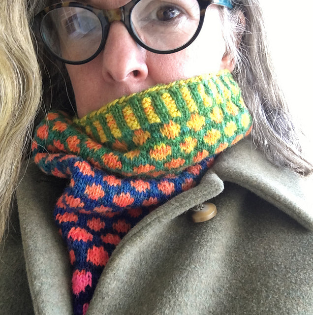 Woman wearing glasses peaks out from behind a spotted and ribbed cowl worn inside a jacket