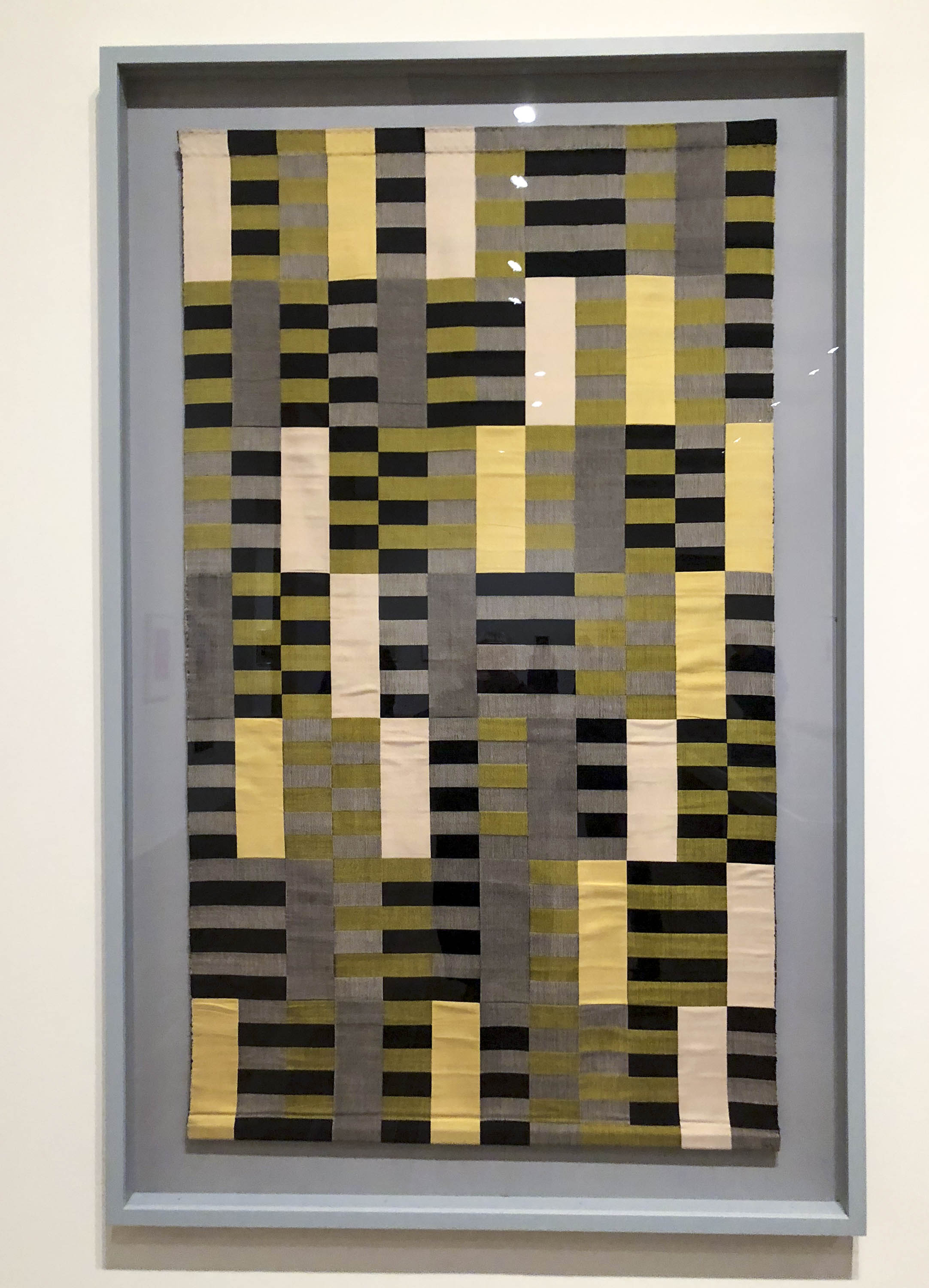 Anni Albers abstract textile panel exhibited at Tate. Four colours in stripes are used to create shifting colours and combinations
