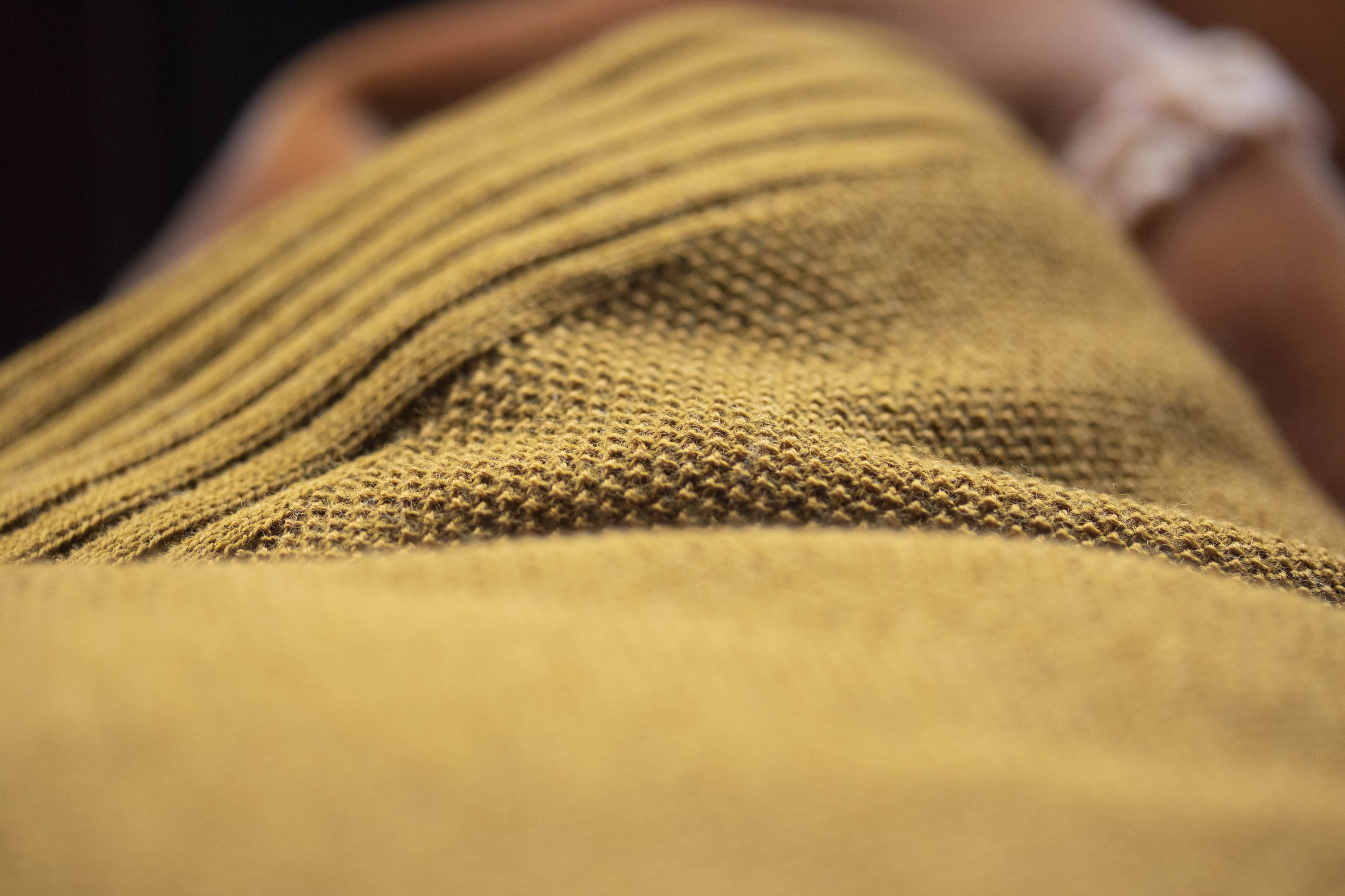 Detail of Saand holiday jumper. Fine merino yarn knitted in moss stitch for a subtle texture. Ribbed detailing. Shown in a yellow ochre