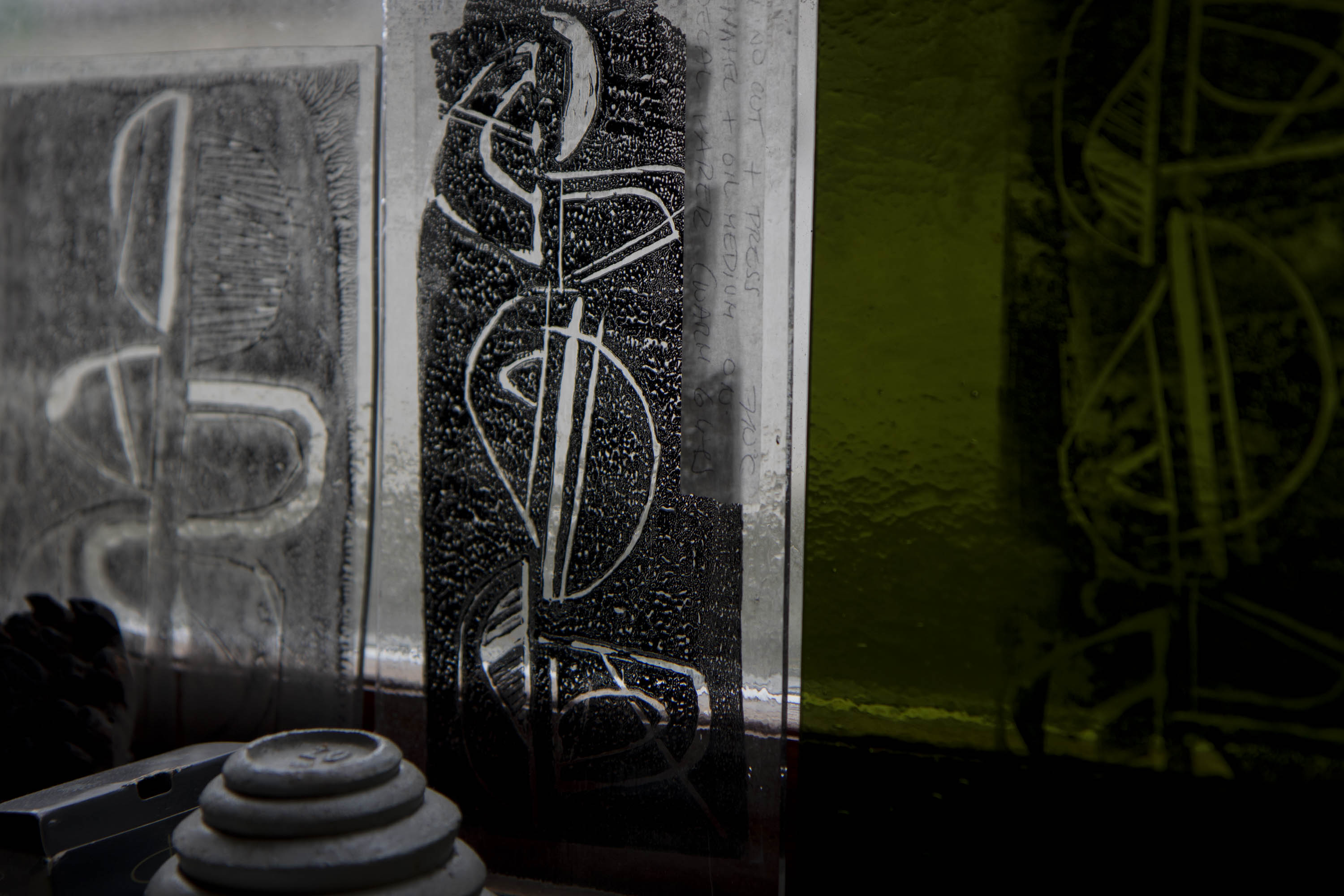 Three linocut prints on glass against a window. The ink is black and shows a reversed-out curvilinear motif. One piece of glass is limey yellow-green