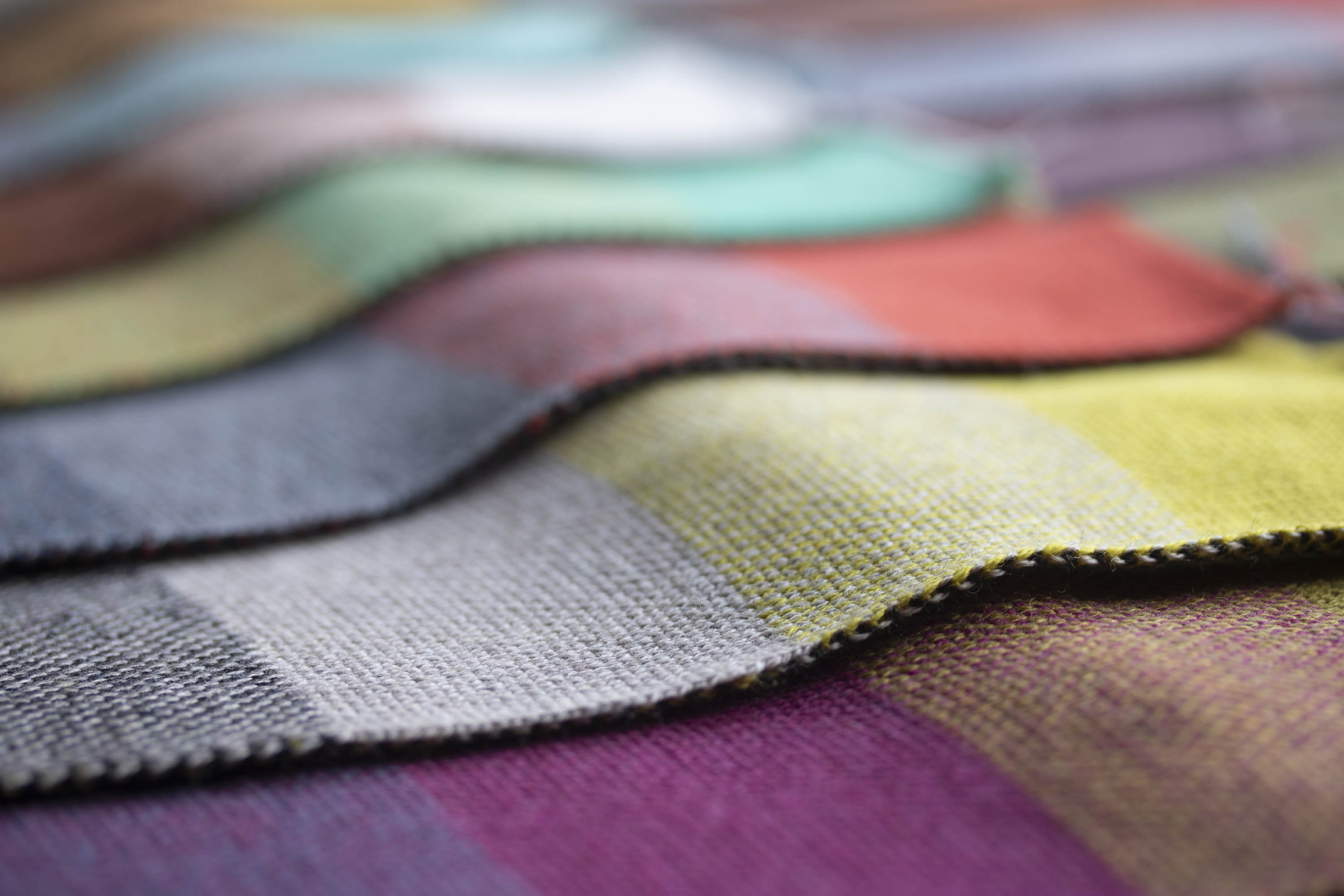 Several swatches of knit, showing overlapping colours using 3 colour of yarn. In the foreground, yellow, grey and black