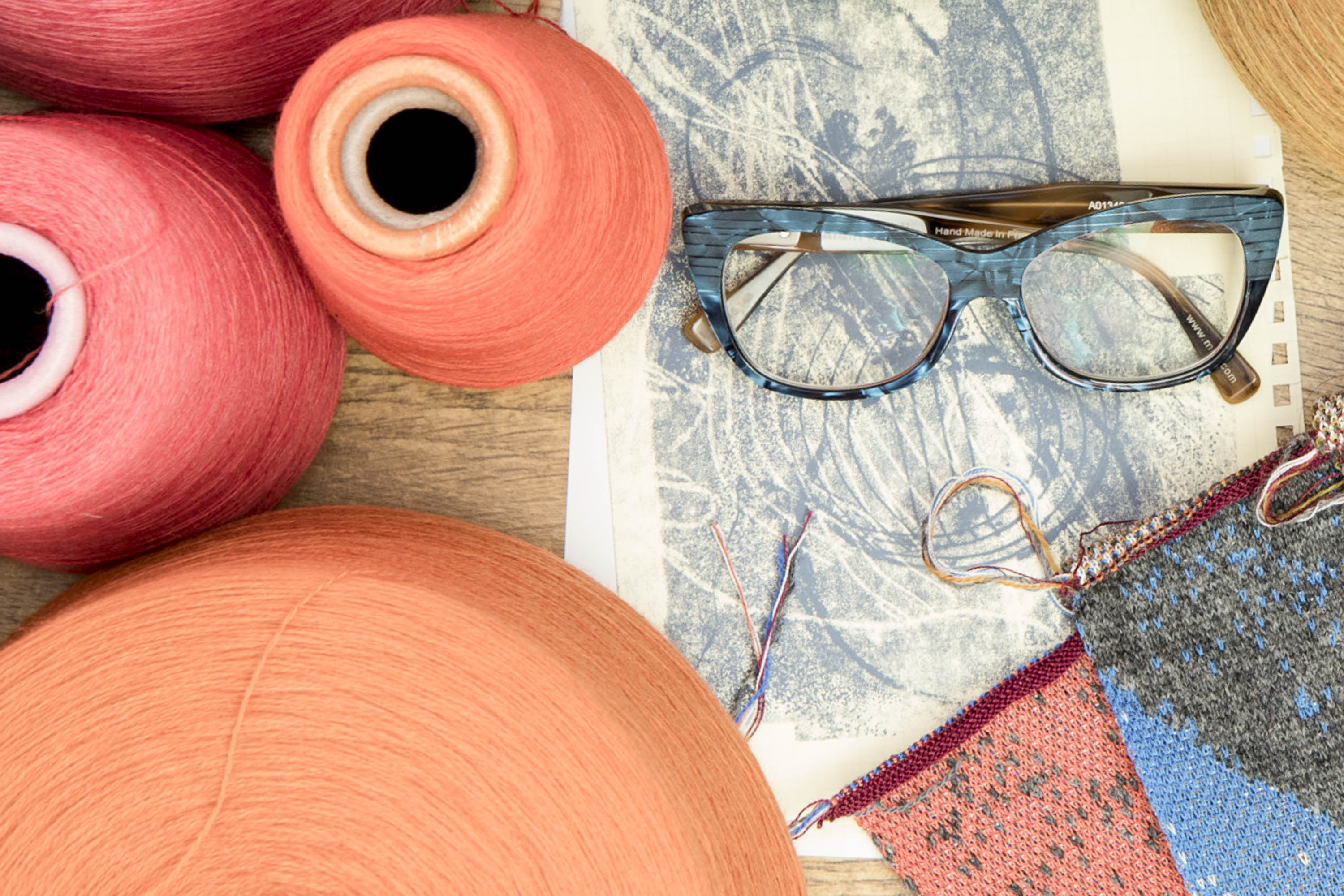 Blue patterned spectacles, a print, cones of yarn, knit sample swatches all laid flat on a table at Nielanell contemporary knitwear studio, Shetland.