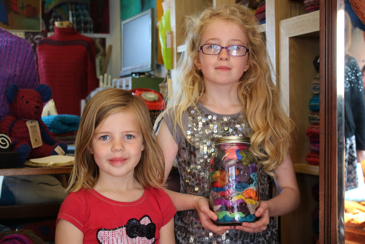 Two young girls hold a jar of cloos of yarn at the Nielanell studio, Shetland