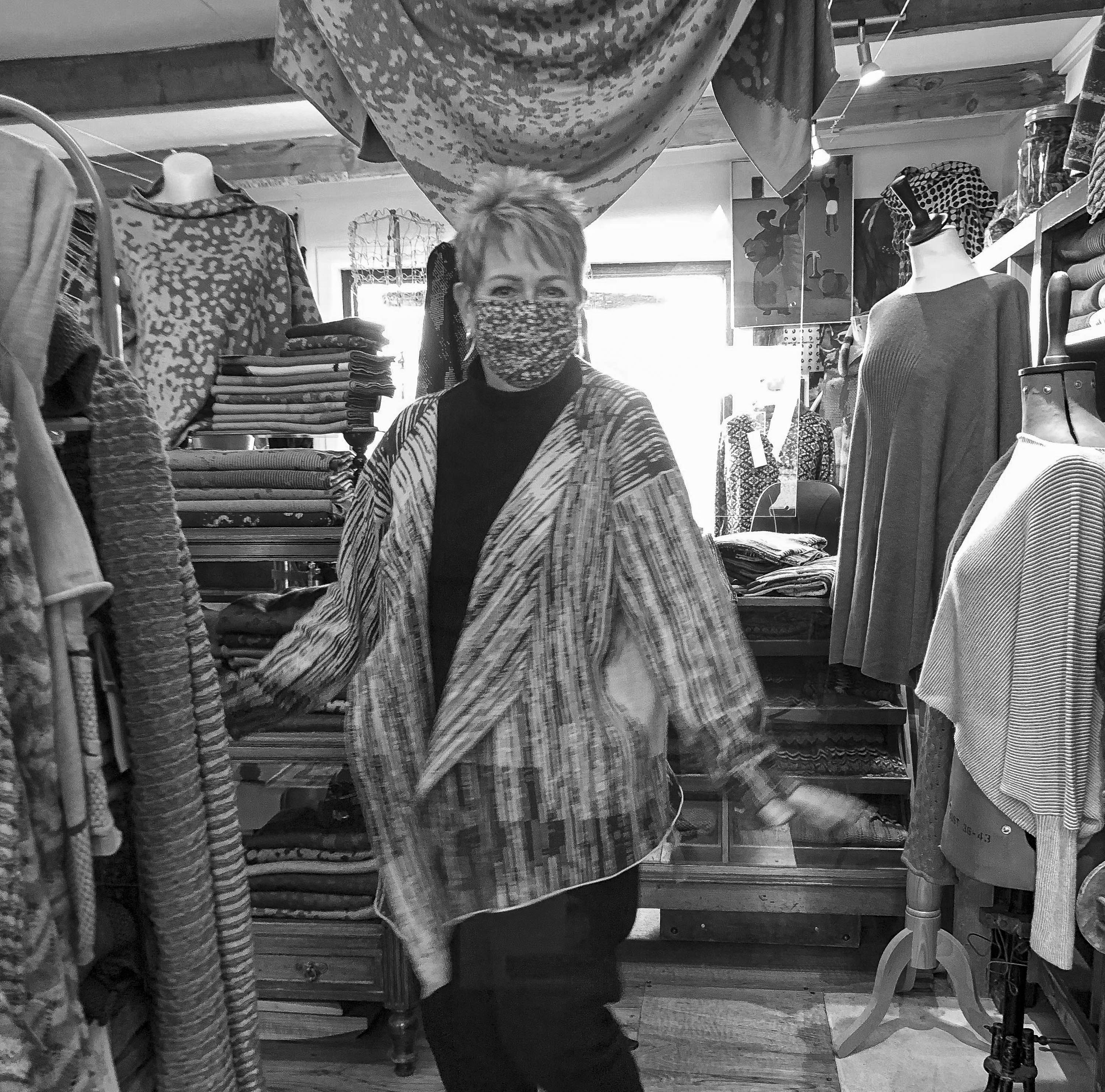 In the Nielanell knitwear studio, Hoswick, a woman wears an abstract, linear pattern knitted jacket. contemporary in style and with wide lapels