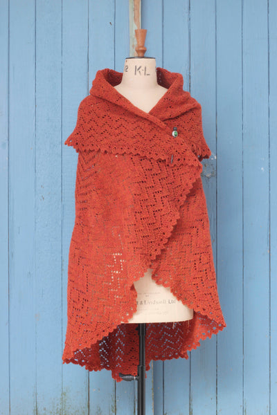 A large, circular hand-knitted lace shawl in rust coloured yarn. Shown on a vintage mannequin, pinned. Against a tongue and groove, blue door.