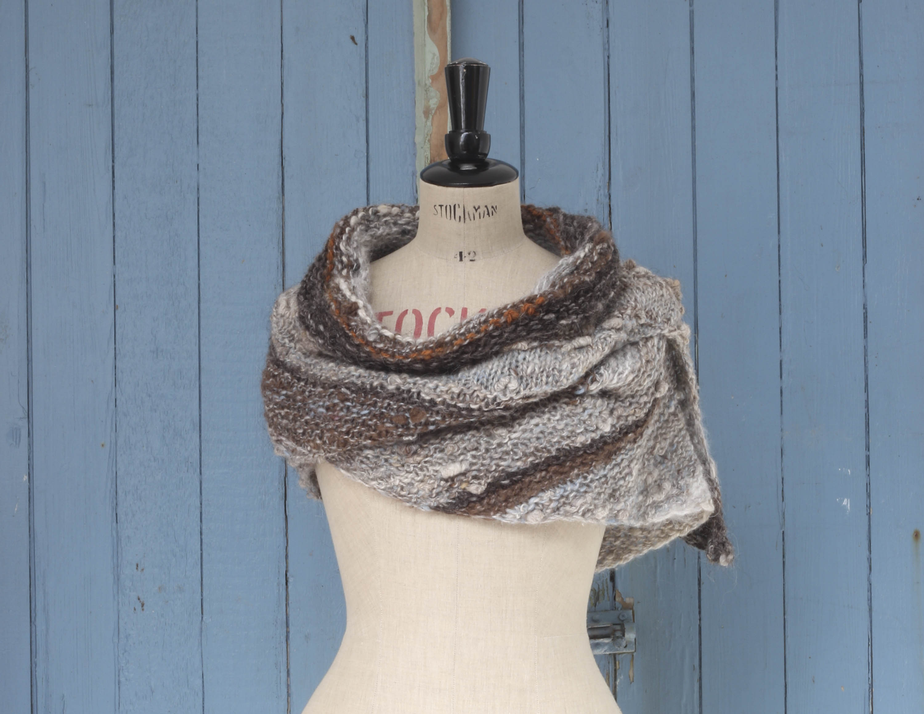 Small shawl knitted in handspun Icleandic yarn in natural colours, photographed on a vintage mannequin against a light blue, panelled door.