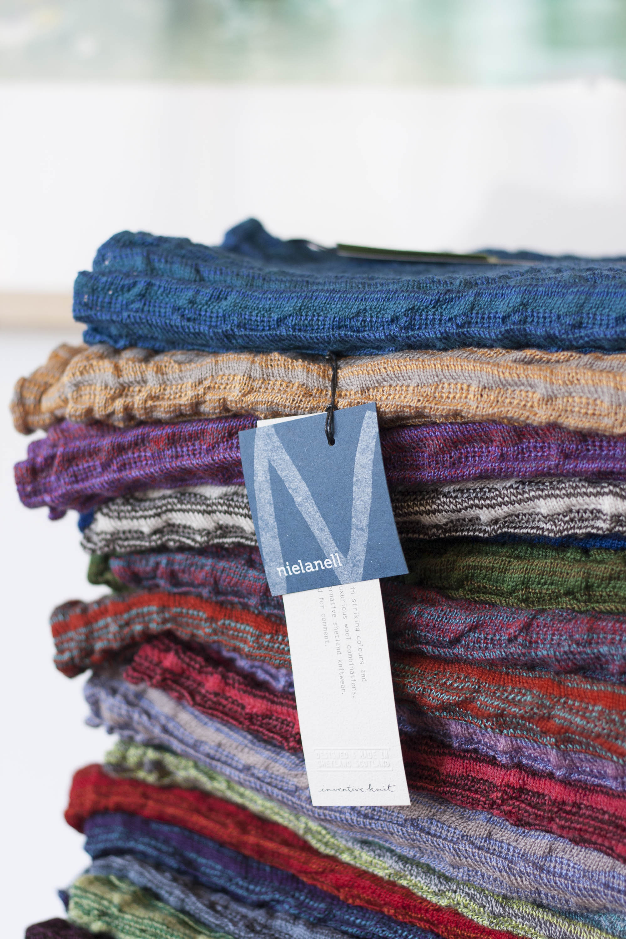 A stack of Rigg capes in the Nielanell studio, Shetland. Many different colours in a ridged, knitted textile
