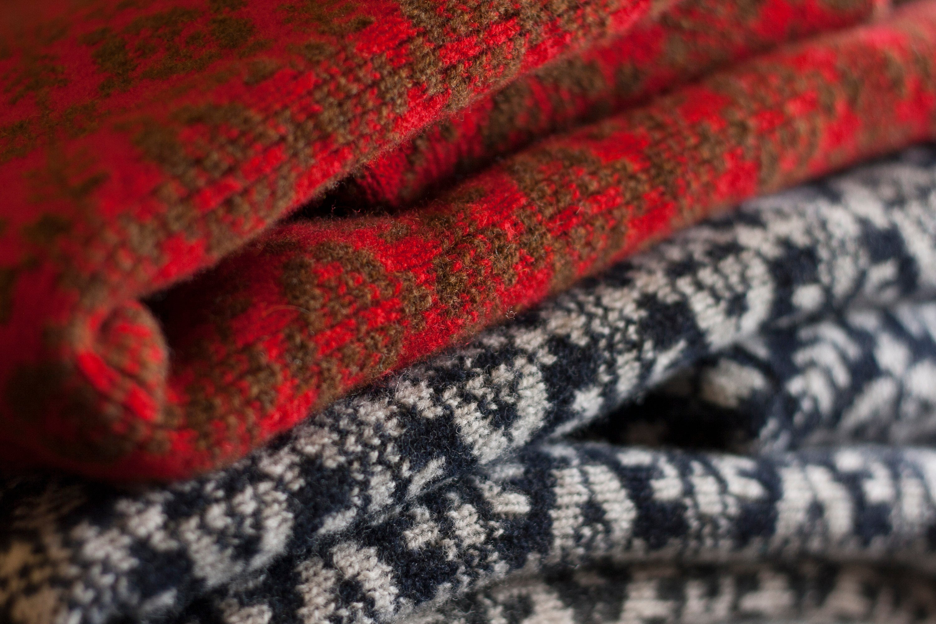 Close up of Fair Isle jumpers at the Nielanell studio, Hoswick, Shetland. One jumper in red and brown, the other in charcoal and very pale grey