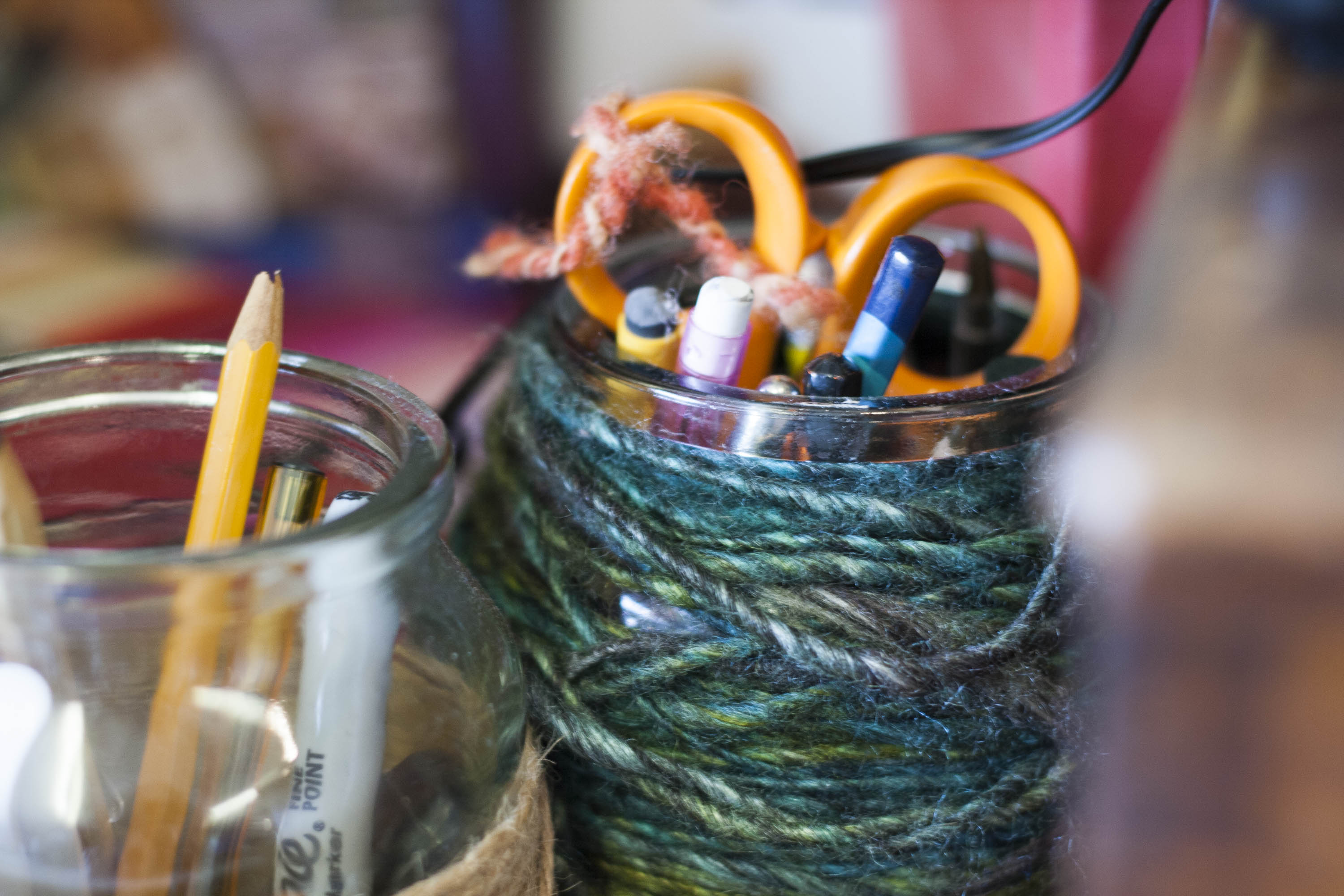 Two jam jars in the Nielanell studio, Hoswick, Shetland, with pencils, pens, scissors etc. One with teal and green handspun yarn wrapped around it