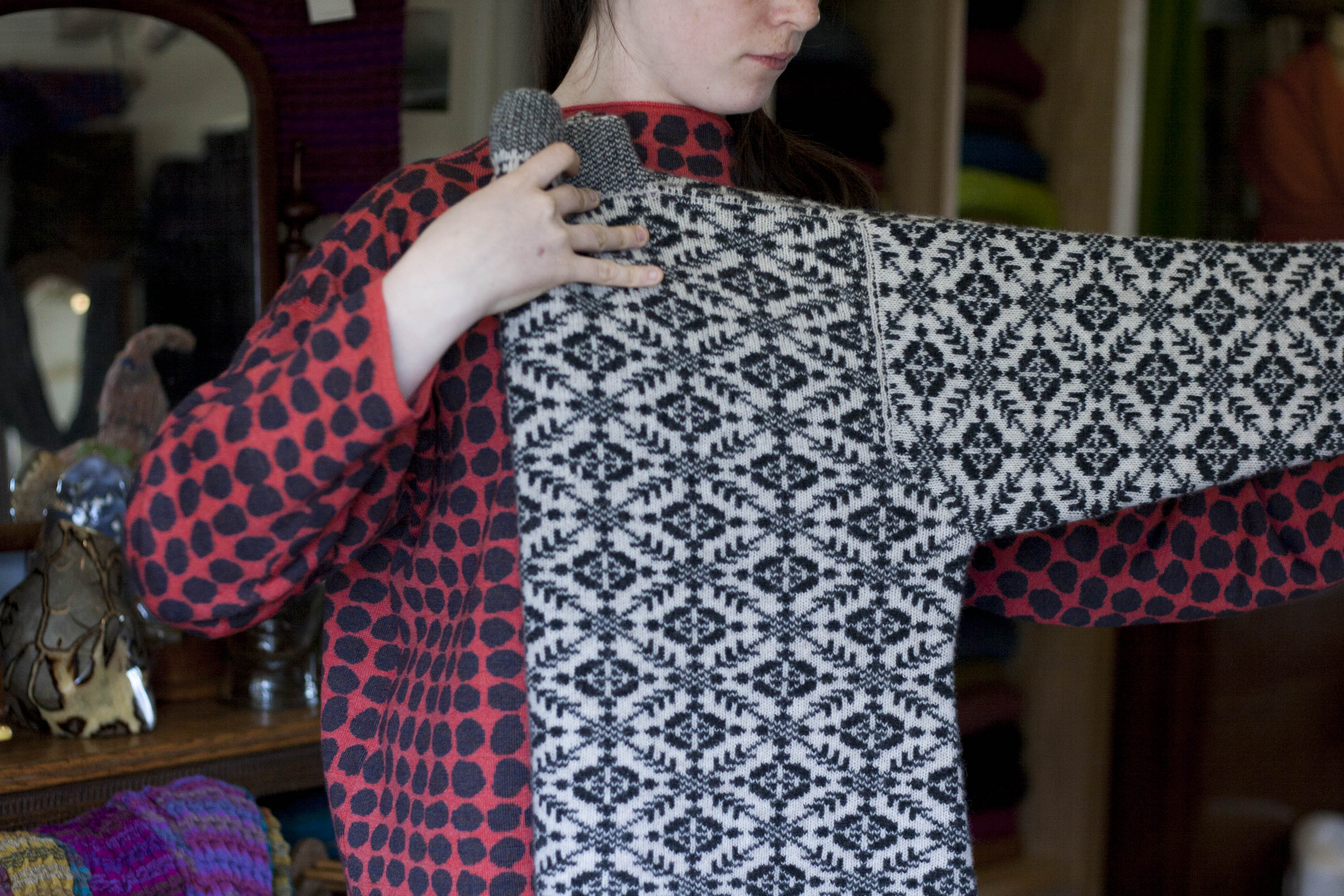 A girl holds a navy and off white patterned Fair Isle jumper by the neck and sleeve, folding it in half