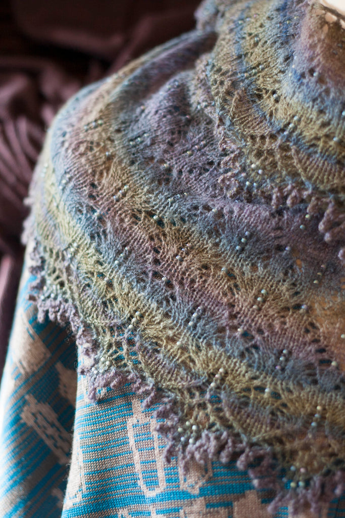 Fine shetland-style lace shawl knitted in hand-dyed, handspun yarn. In soft purples and blues with some beads.