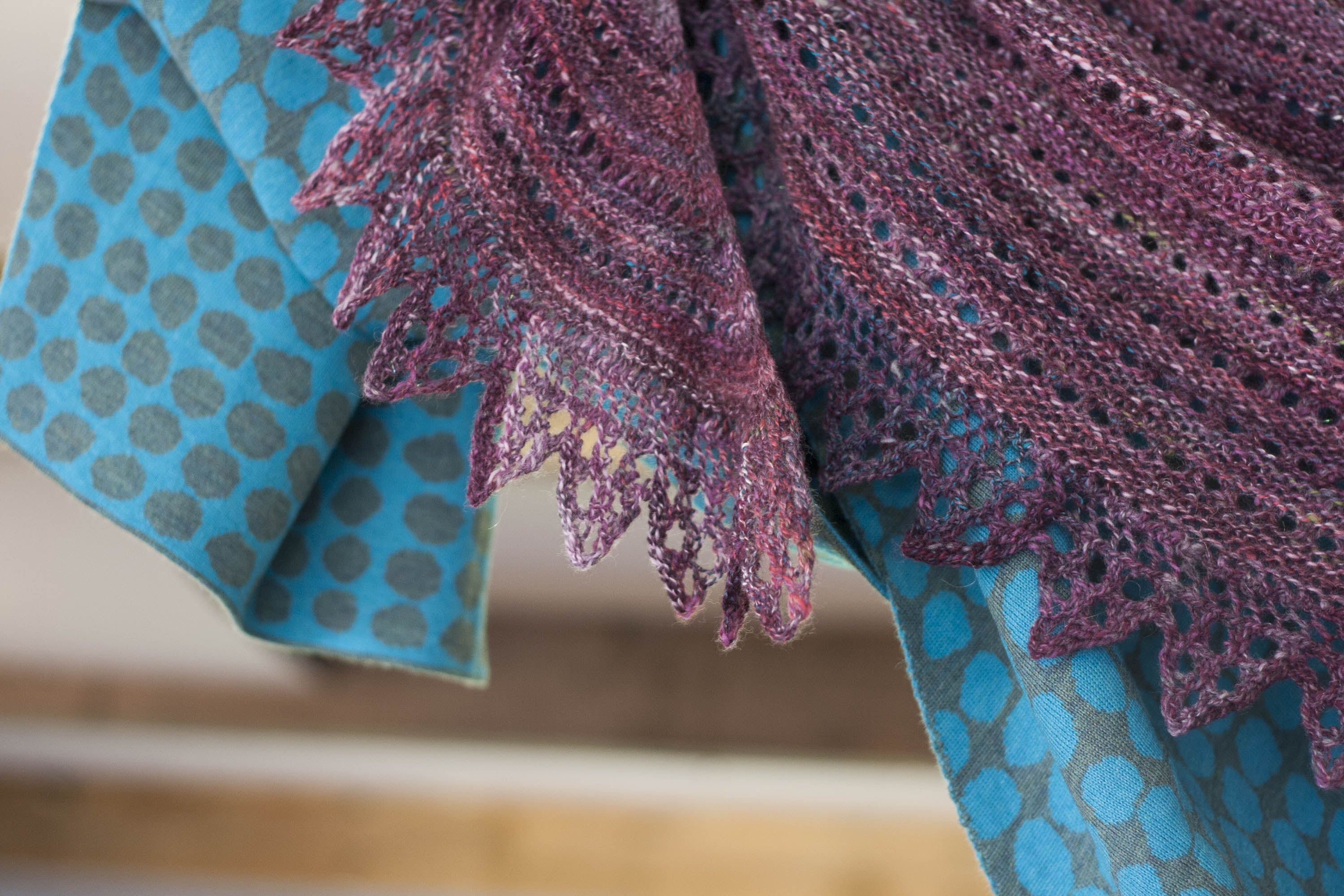 Handknitted shawl in handspun yarn in purples and plums. With lace edging. Hangs over a contemporary Nielanell shawl in blues with an abstract pattern.