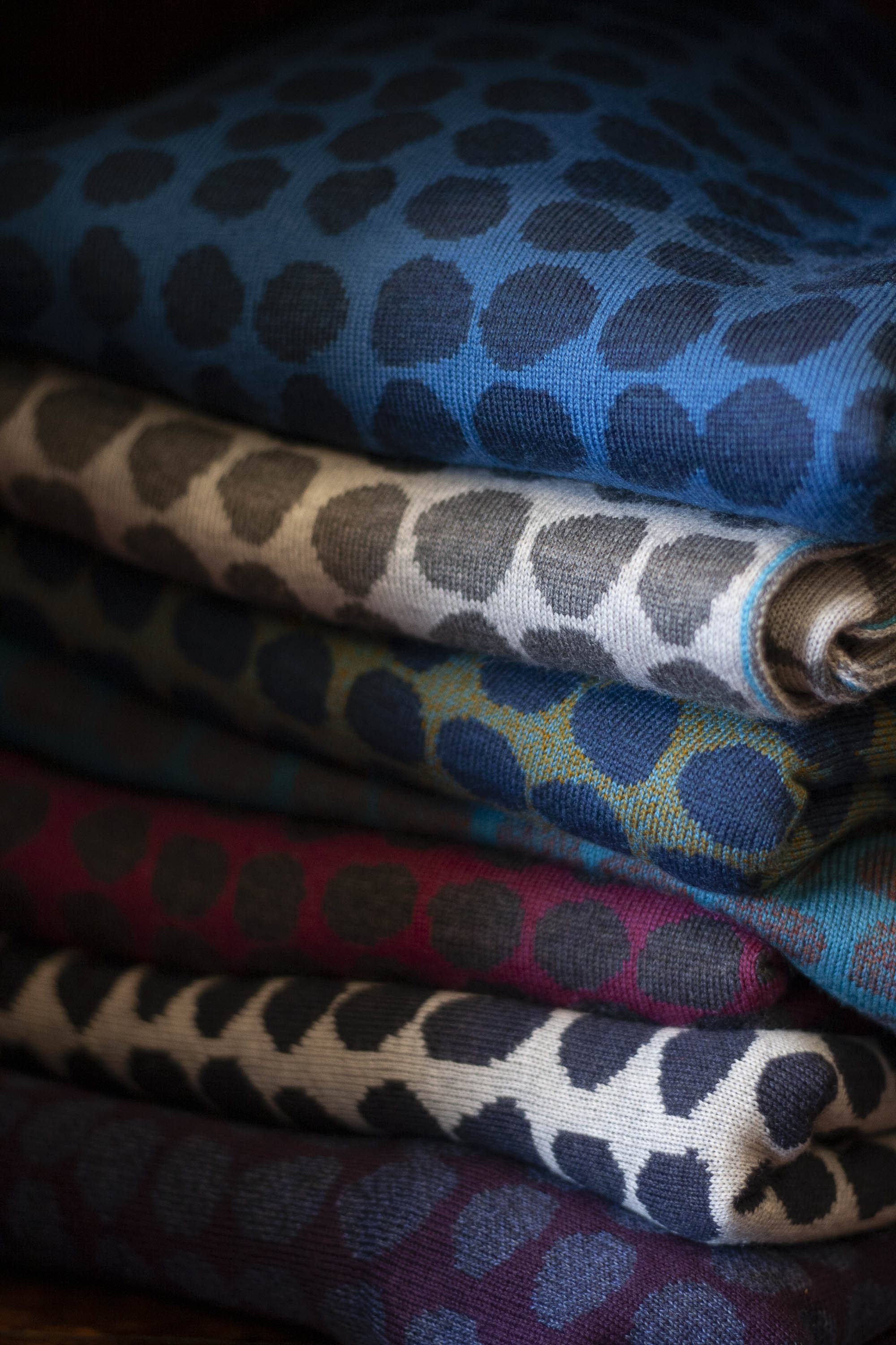 A stack of contemporary Scottish knitwear in vitamin colours. Irregular dots in two colours in each pieces. Blues, greens, berry colours and neutrals