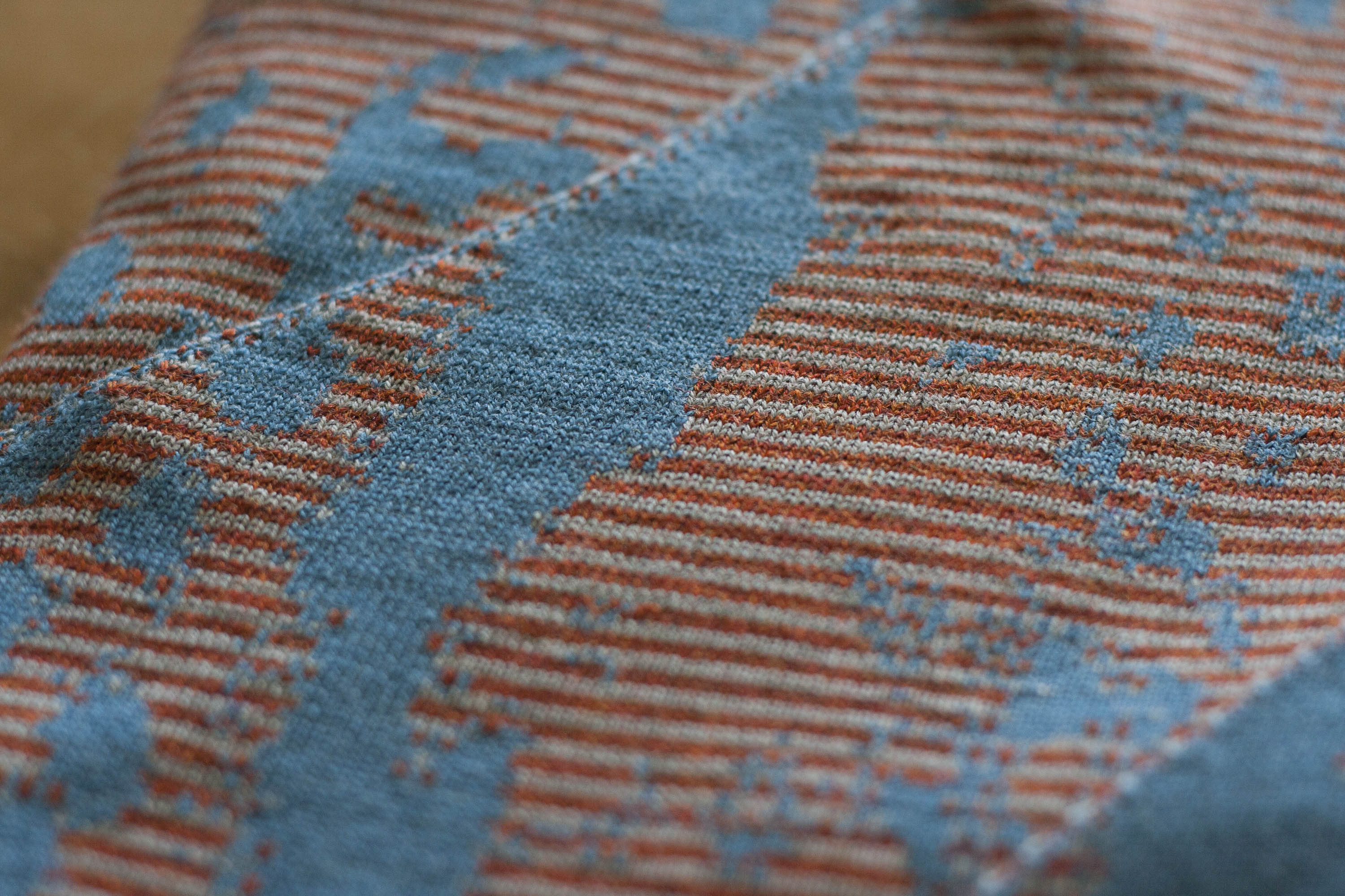 Detail of striped Marlet textile in blues and rusts. Mottled abstract textile design