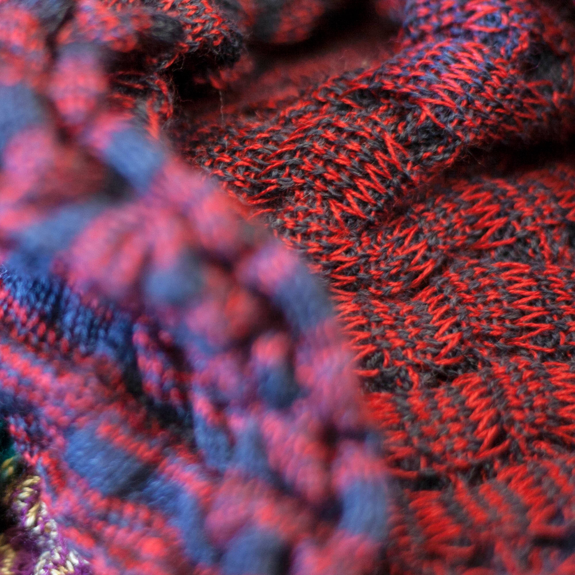 detail and back of rigg vaarie jacket. Red and blue stripes in a ridged, scrunchy textile
