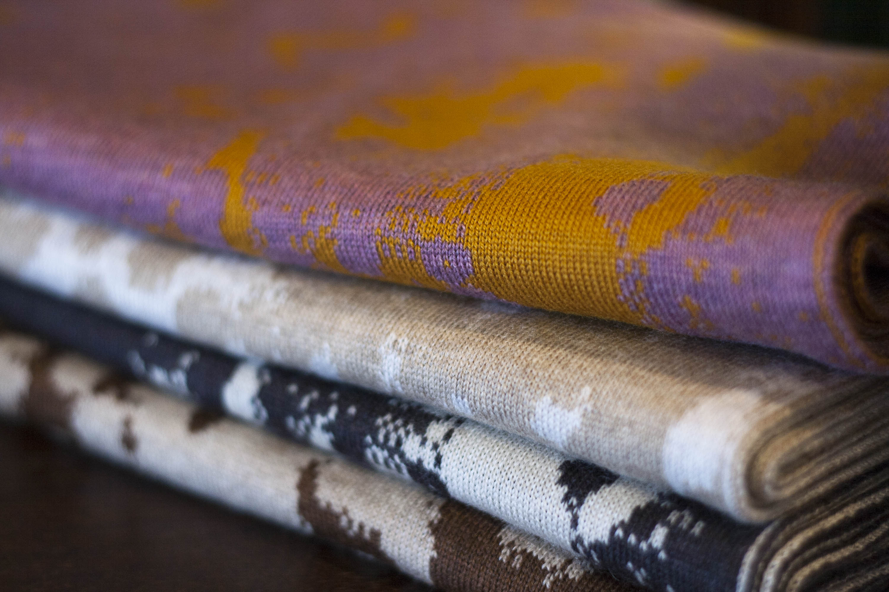 Stack of contemporary Scottish knitwear in extra fine merino wool, these are cowls in an abstract mottled pattern