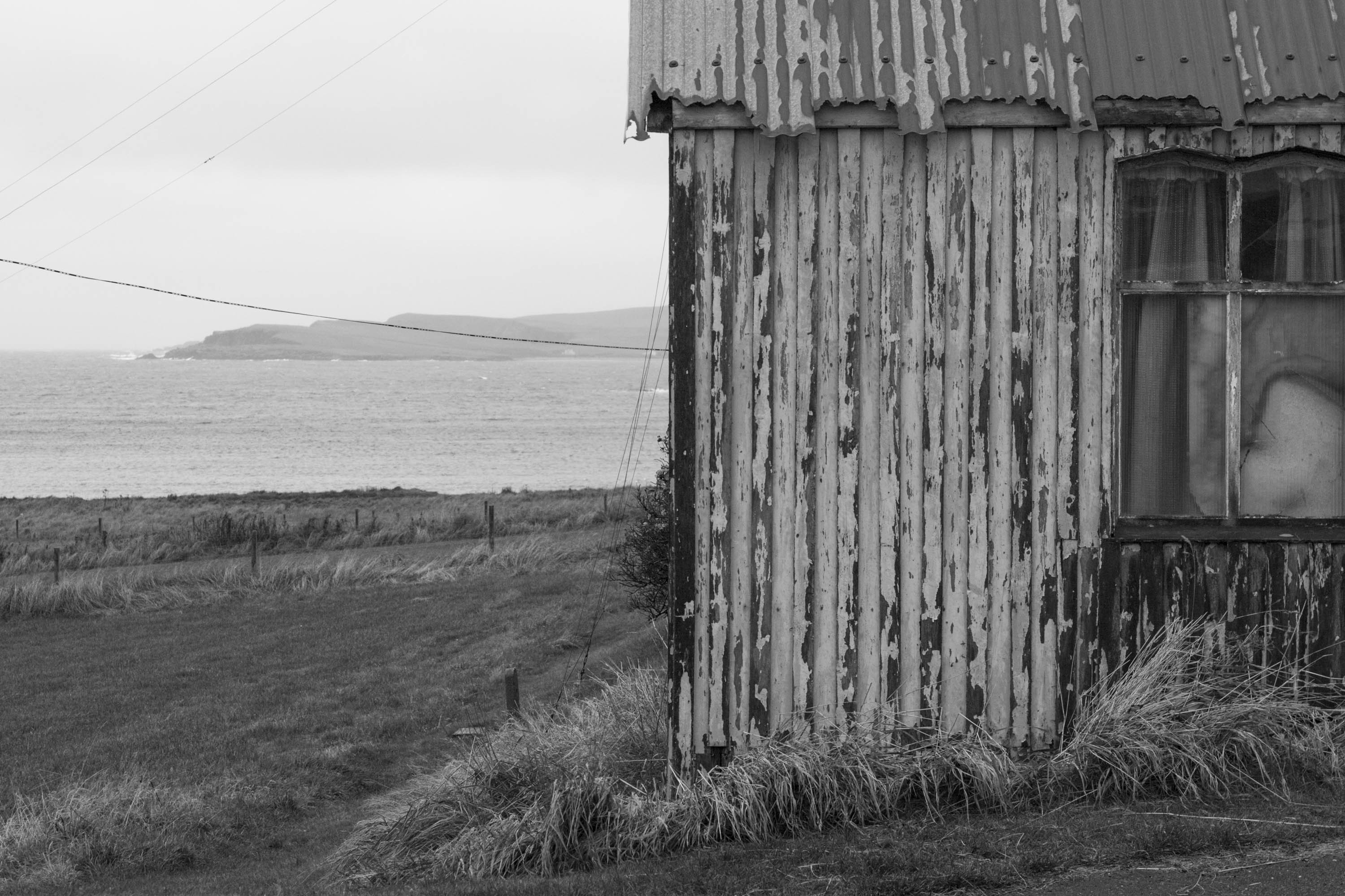 Gospel Hall in Hoswick, Shetland. A small, old wooden building with a corrugated tin roof. The tin is worn, with a jagged edge. Behind a view to the sea and Levenwick