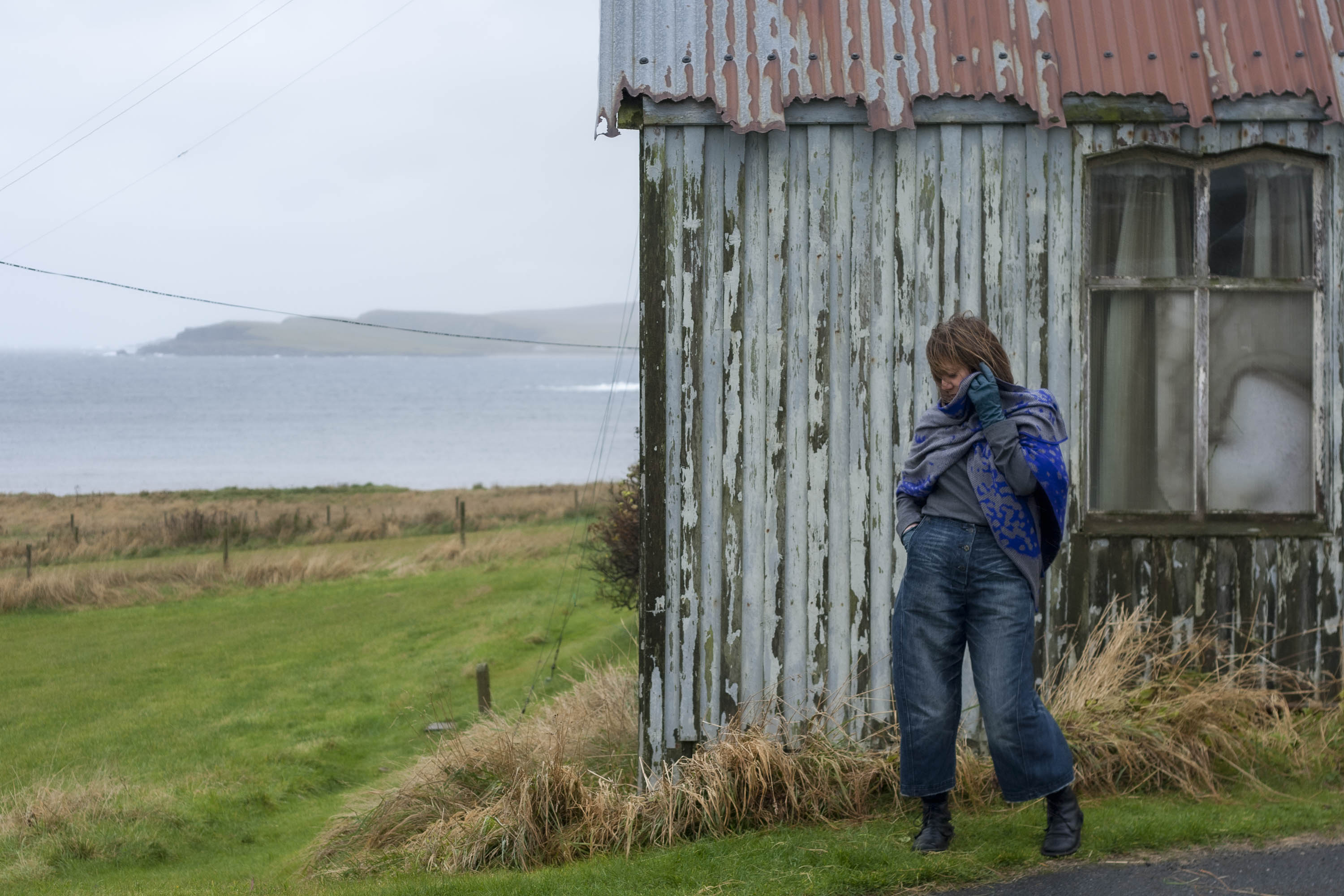 At the Gospel Hall, Hoswick, Shetland - a small, old wooden building with a rusted tin roof. In front of the building a woman stands with a grey and electric blue wrap and indigo loose jeans
