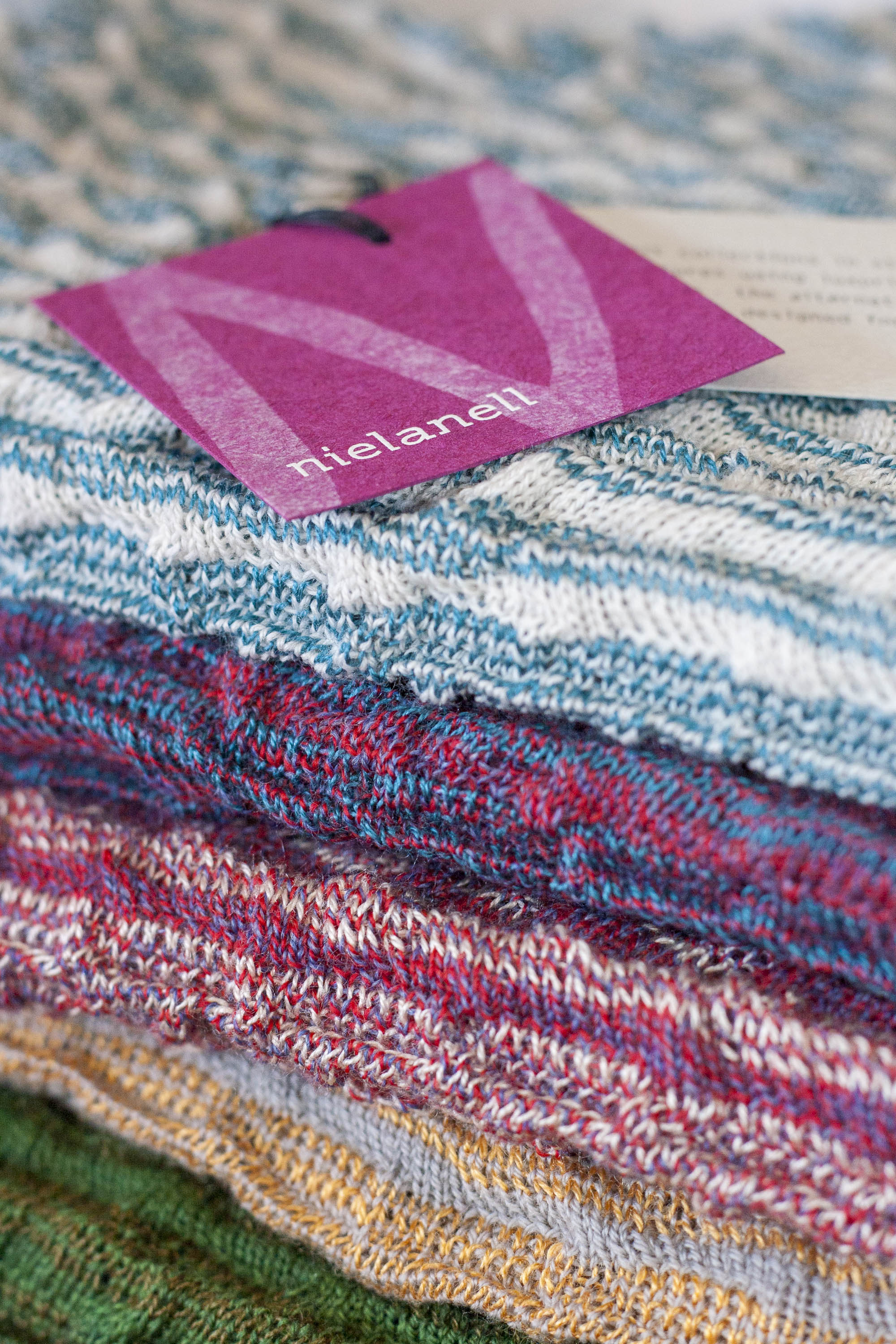 Stack of contemporary, colourful knitwear in the Nielanell studio, Hoswick, Shetland. Greens through pinks to blues. A swing ticket in recycled card is on the top garment. Pink card with white N and logo.