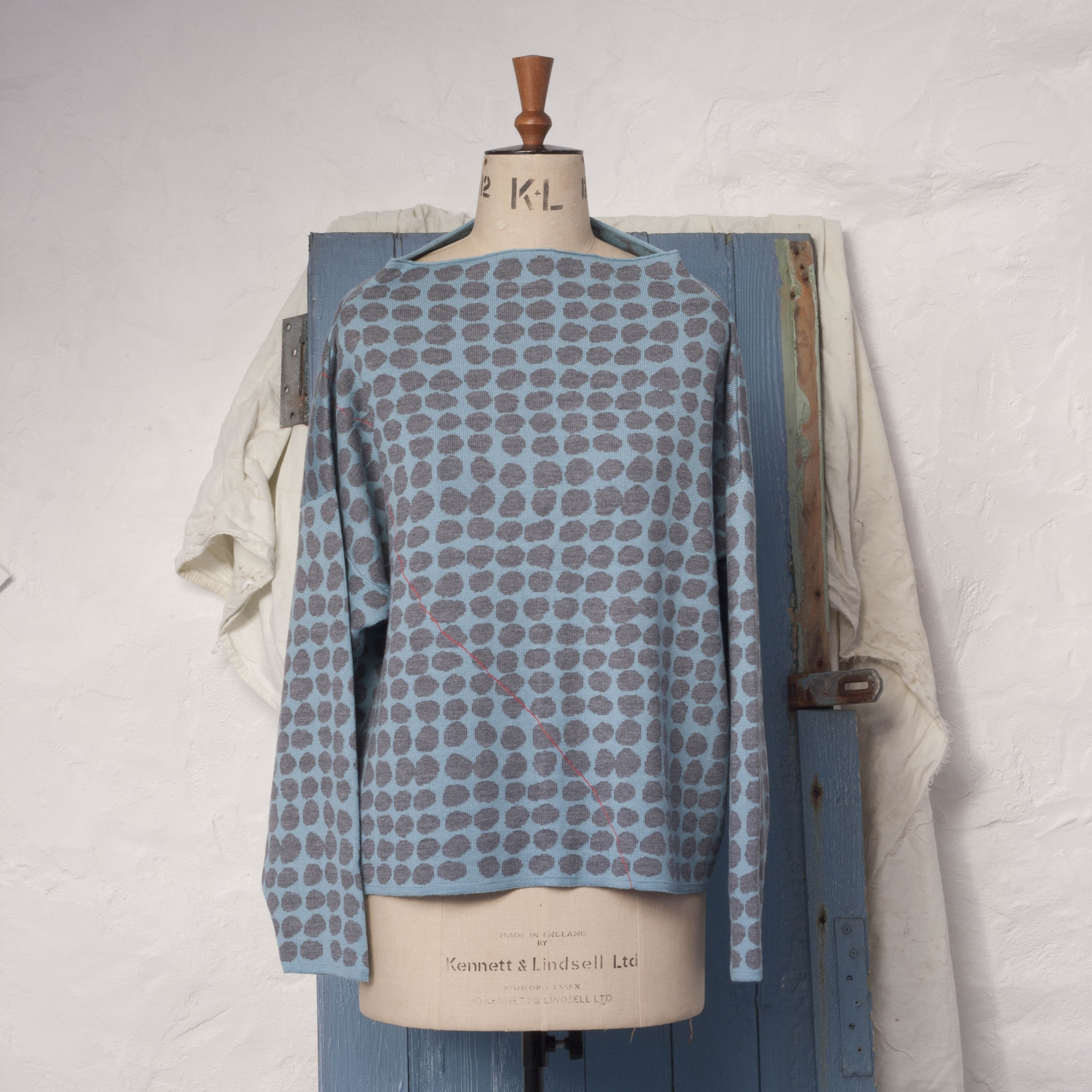 Ebb-stanes contemporary Scottish jumper. A pattern of pebbles in blue and marl, with coral individually drawn line