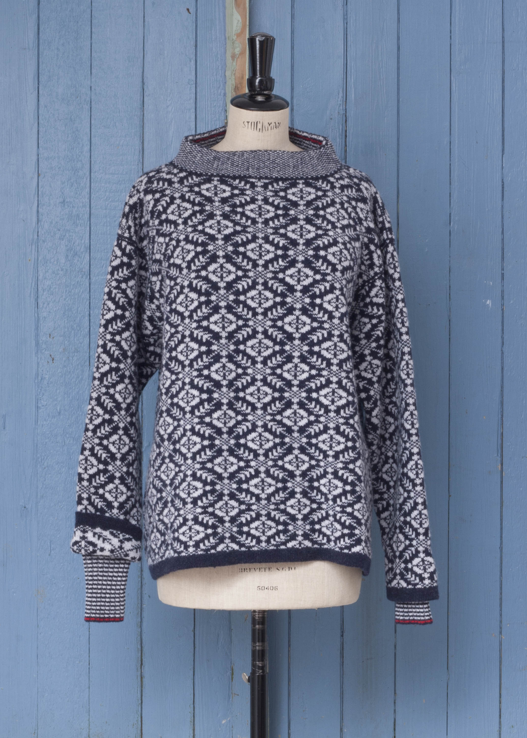 Shetland Smookie jumper with all-over Fair Isle pattern in navy and feather. Stand up neck and storm cuffs. Shown on vintage mannequin against blue panelled door.
