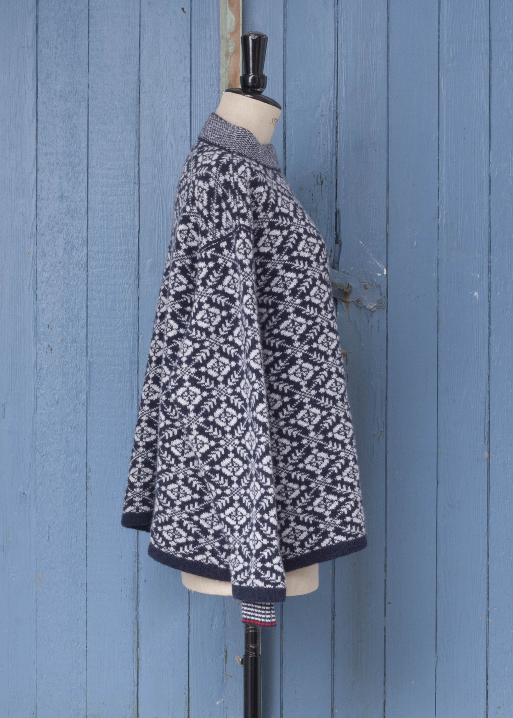 Side view of Fair Isle style jumper in navy and feather pale grey. All over pattern. Shown on a vintage mannequin against a blue wood panelled door.