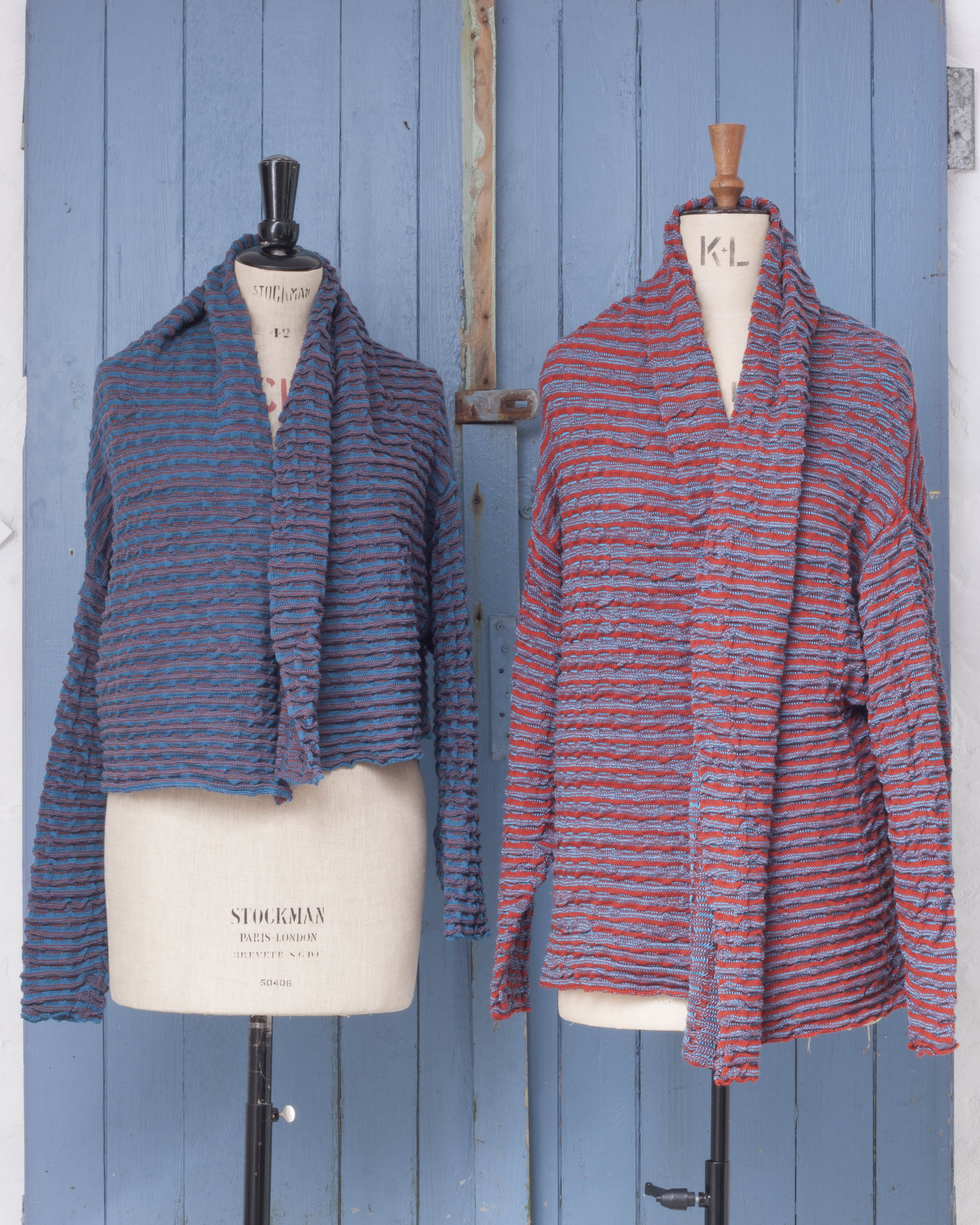 Two knitted, lightly ridged jackets on vintage mannequins. on the left the blue with hint of purple jacket is shorter. On the right, the pink with blue jacket is longer