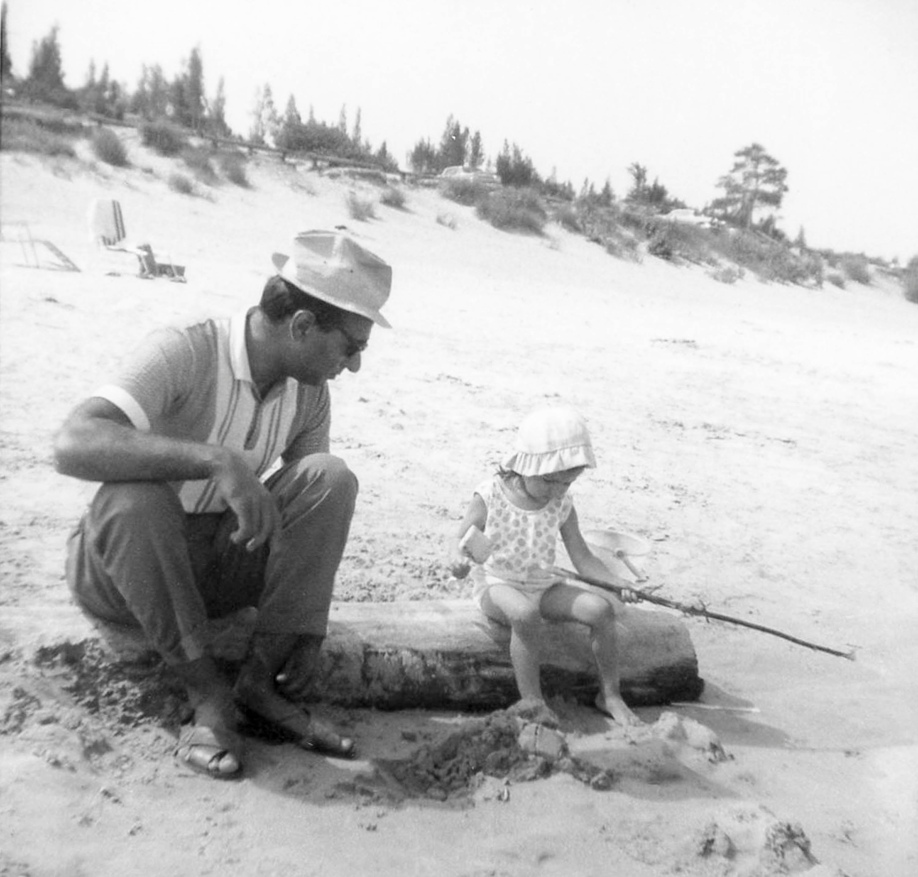 A father and his young daughter play at fishing on a beach. They sit on a log using a stick as a log and are dressed for summer, both wearing hats