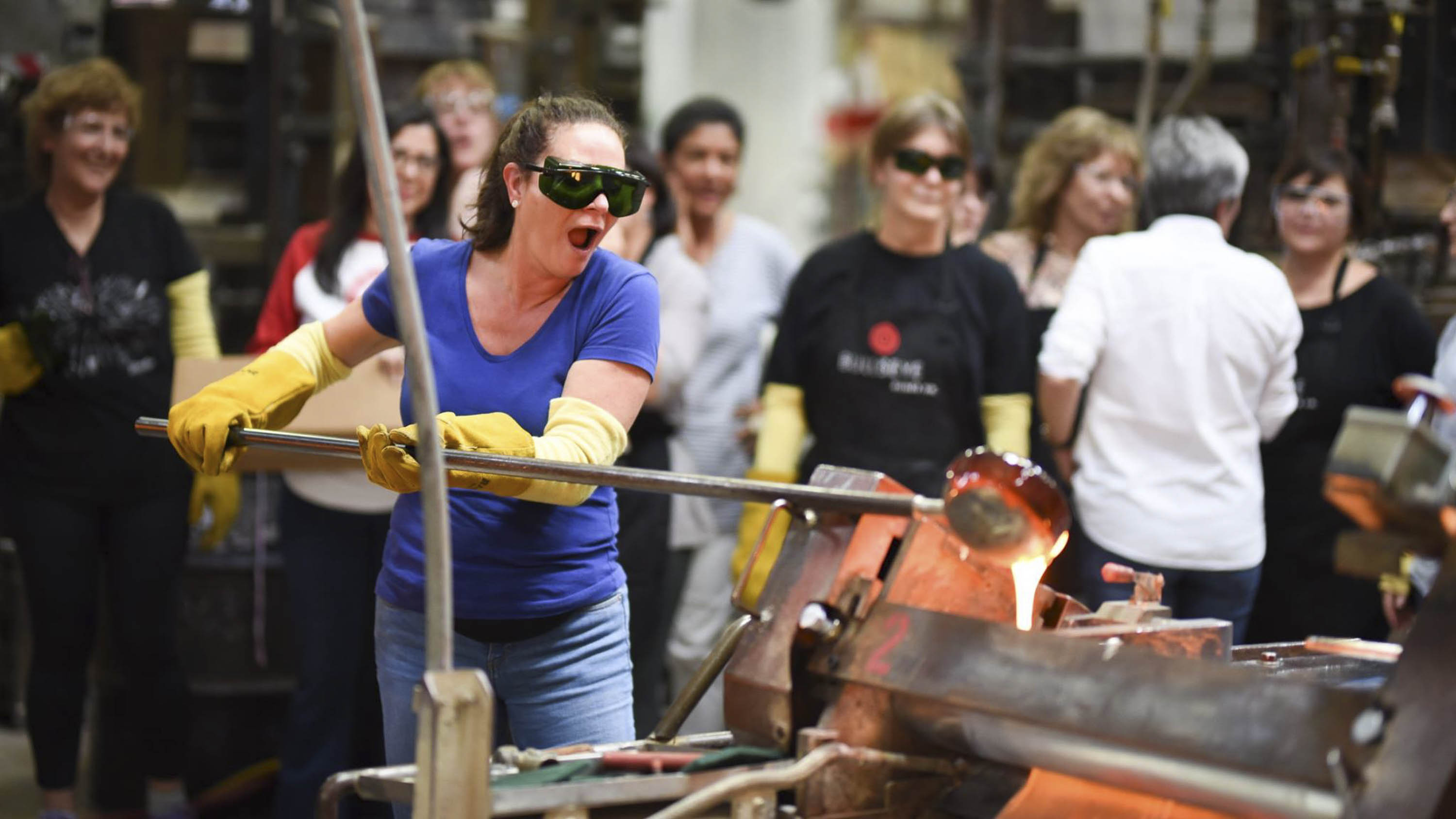 Glass-making at a workshop. A woman wearing safety glasses holds a long rod with molten glass on the end