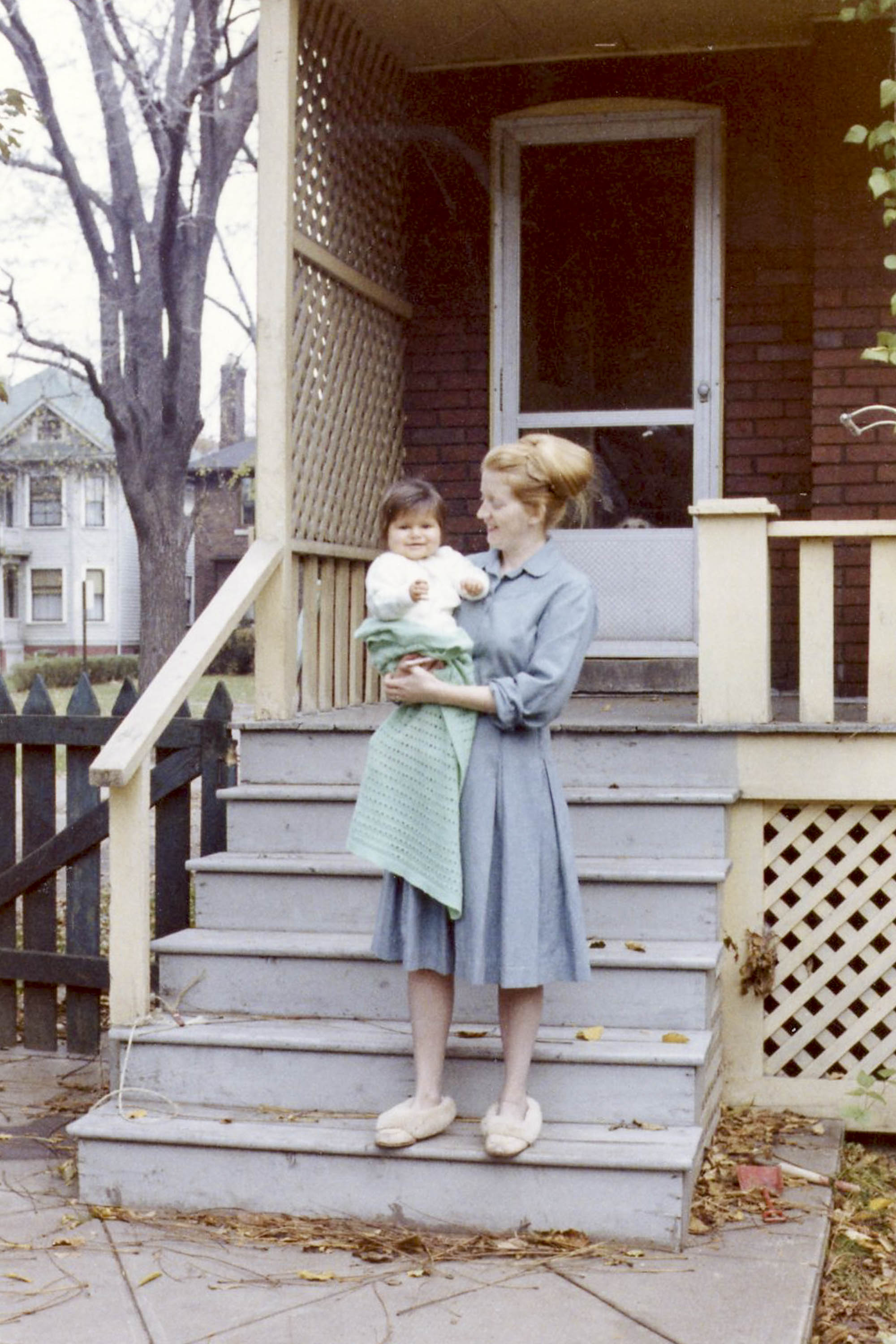 A woman and baby on the steps of a house in Canada. 1960s.