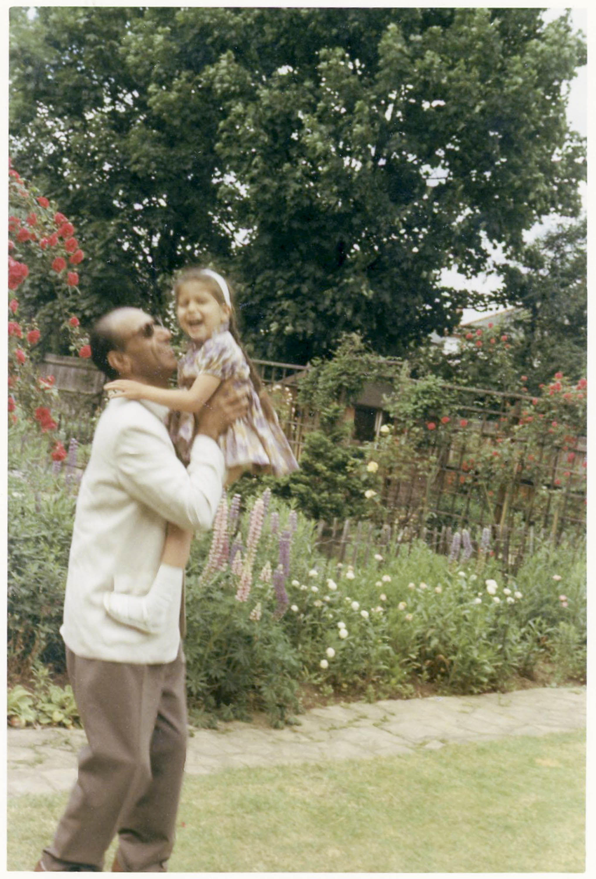 A young girl and her father play in a garden, he lifts her up high. Herbacious border in background. She is wearing a summer dress, he is in brown slacks and a cream cardigan.