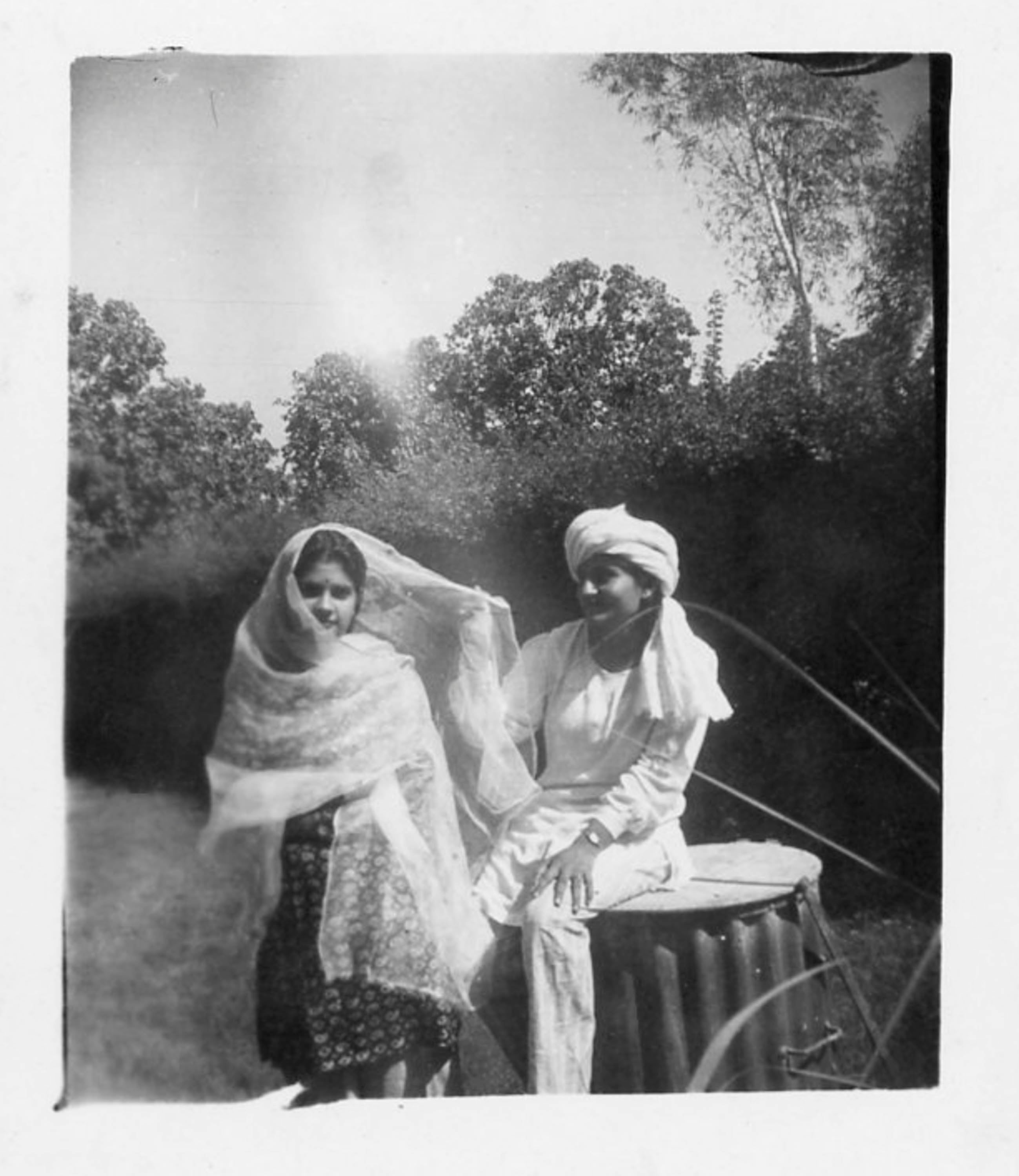 Black and white image of a young man and woman in a garden, in India. She wears a fine shawl around her head and shoulders, he wears white scarf around his head