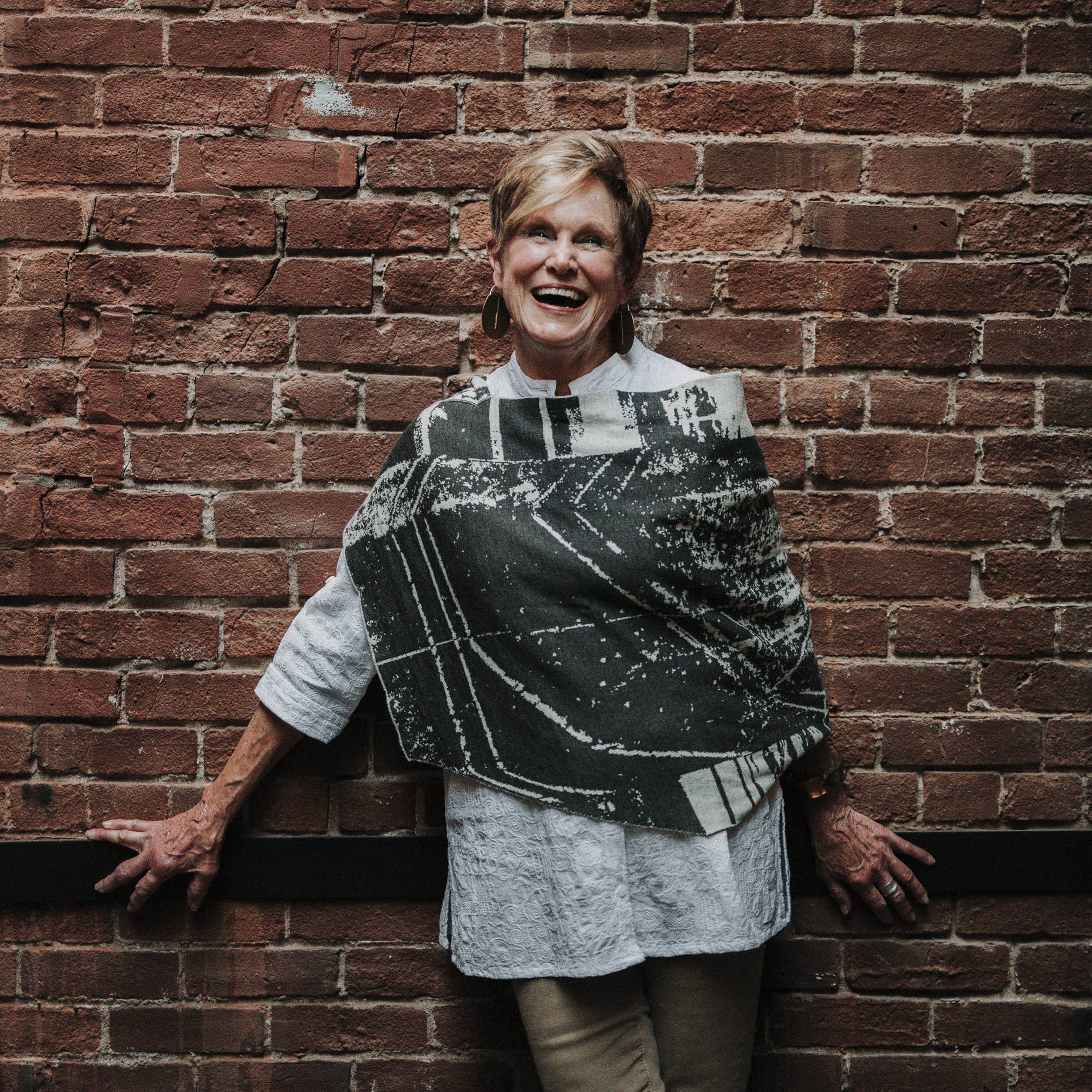 Contemporary Scottish knitwear - a cape-poncho in charcoal grey and stone white. A woman wears this while laughing, standing against a brick wall.