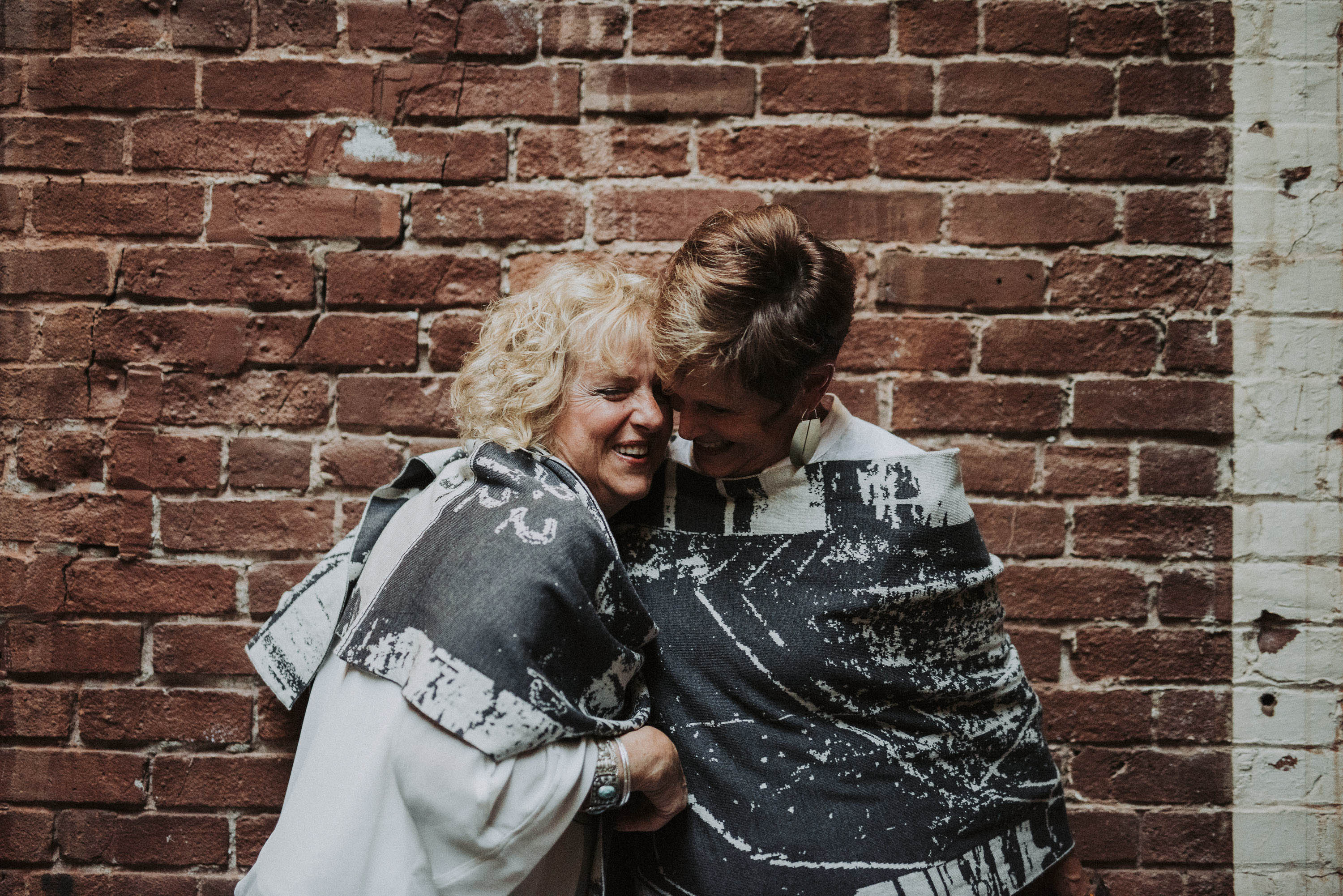 Two women wear contemporary knitwear in charcoal grey and stone white, with abstract patterning