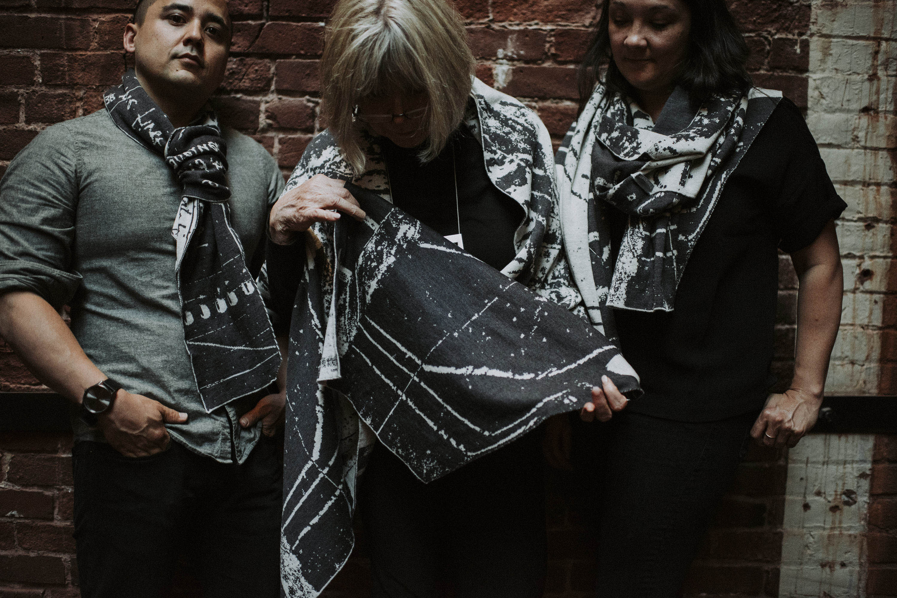 A man and two women wearing pieces from the Nielanell Byre collection of contemporary Shetland knitwear. Charcoal and stone white yarn with abstract motifs and some lettering knitted into the pattern.