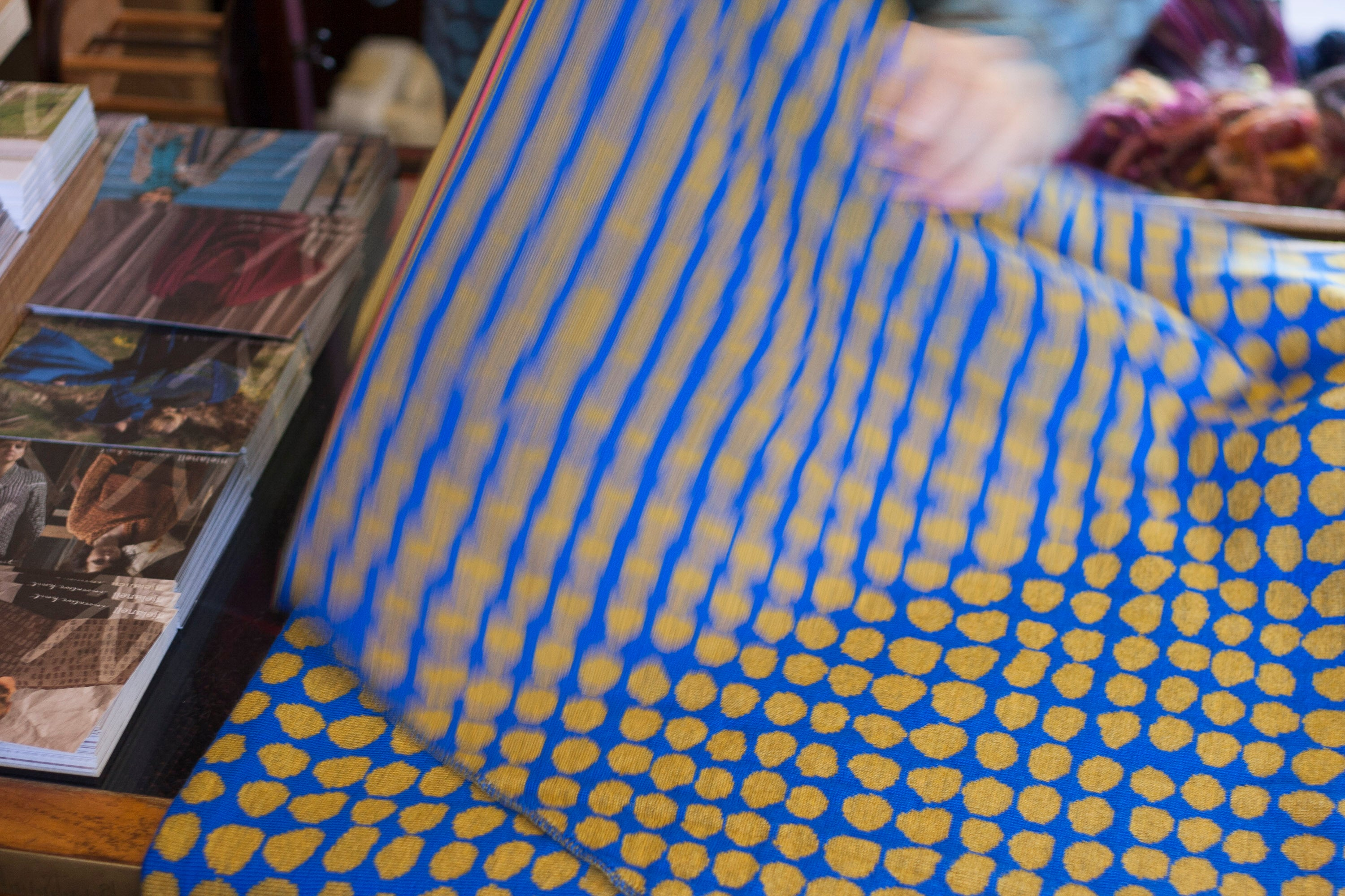 Folding a shawl in gold and blue irregular spot design on a shop counter. Hand visible and fabric in motion. At the Nielanell knitwear studio, Shetland