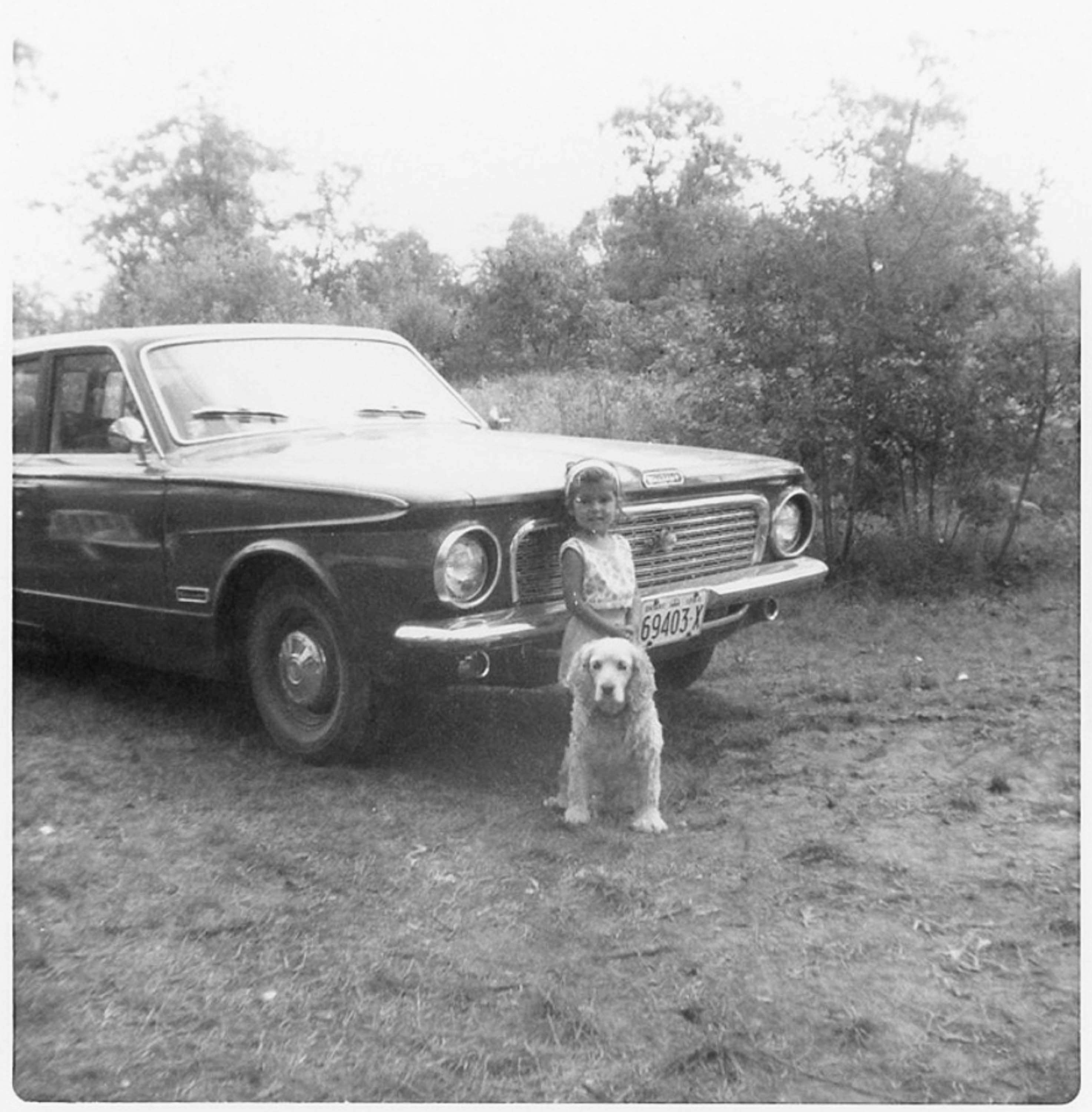 Black and white photograph of young Niela, standing in front of a car with her dog - a spaniel