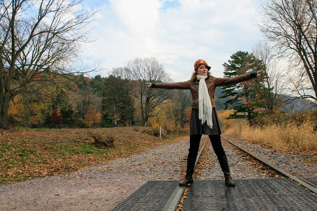 A 23 year old Adrianne outside in the fall on some railroad tracks