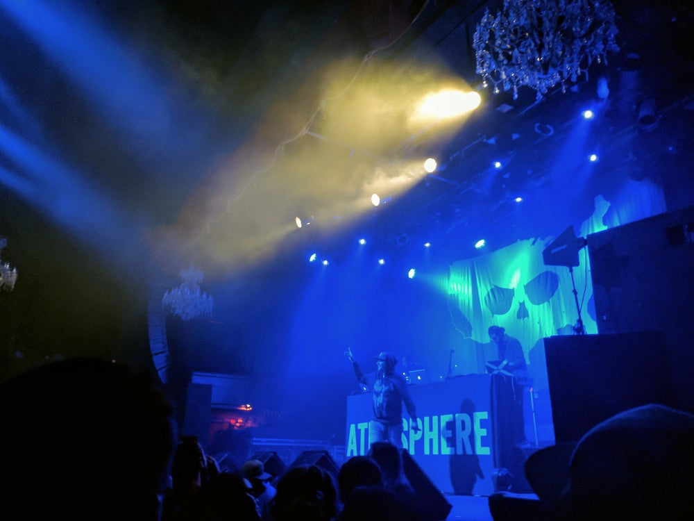 The artist Atmosphere on a blue lit stage