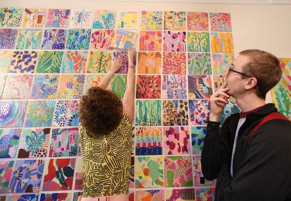The artist pulls a mini painting off the grid wall for a customer