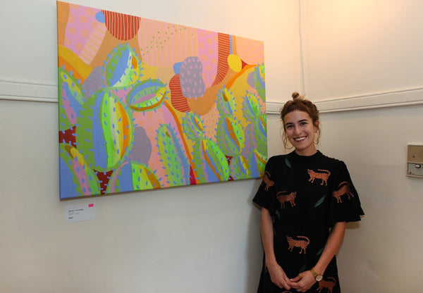 A customer poses with a large painting of cacti