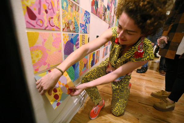 The artist pulls a mini painting off the wall