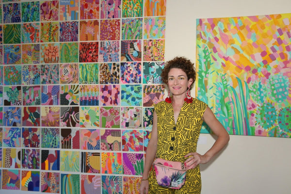 The artist in front of 100 mini paintings