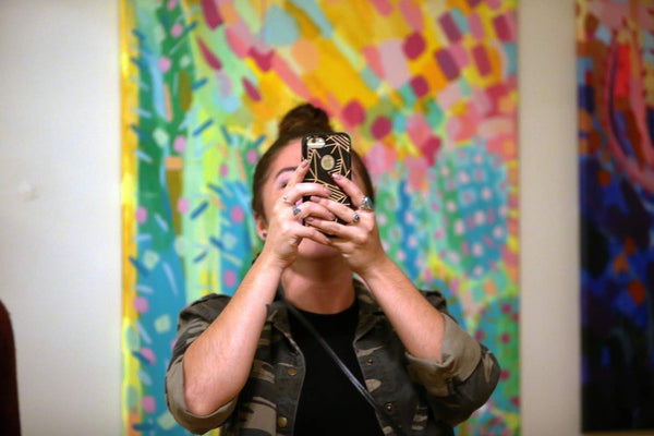 A customer takes a picture of the art with her phone