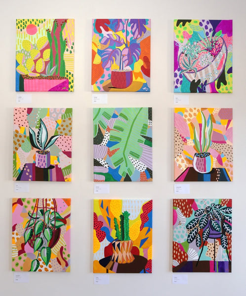 9 paintings on a wall of different plants