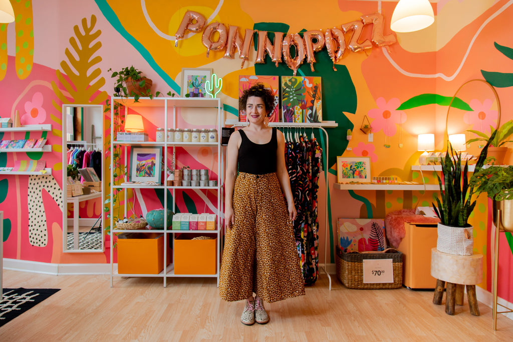 the artist stands in front of retail shelves at her shop, the ponnoplace