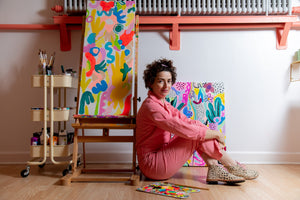 The artist is sitting on the floor in a pink jumpsuit next to one of her paintings.