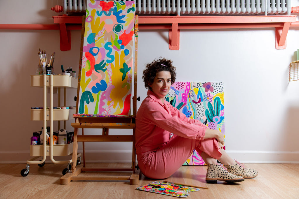 the artist sits on the floor wearing a pink jumpsuit, an unfinished painting sits on an easel behind her.
