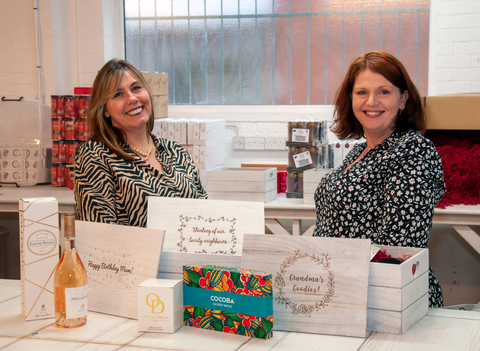 Artisan Directors Caroline and Jo in warehouse surrounded by hampers and personalised lids