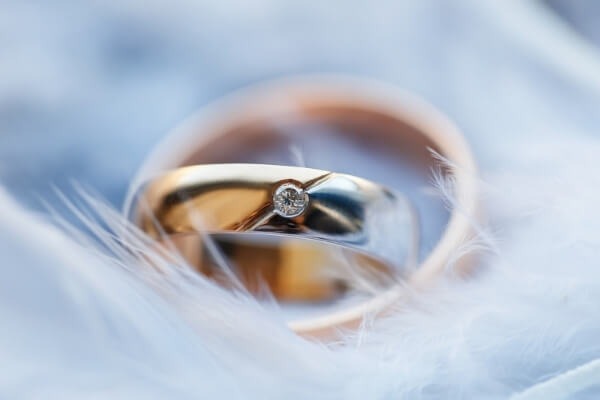 gold-engagement-rings-on-white-feathers